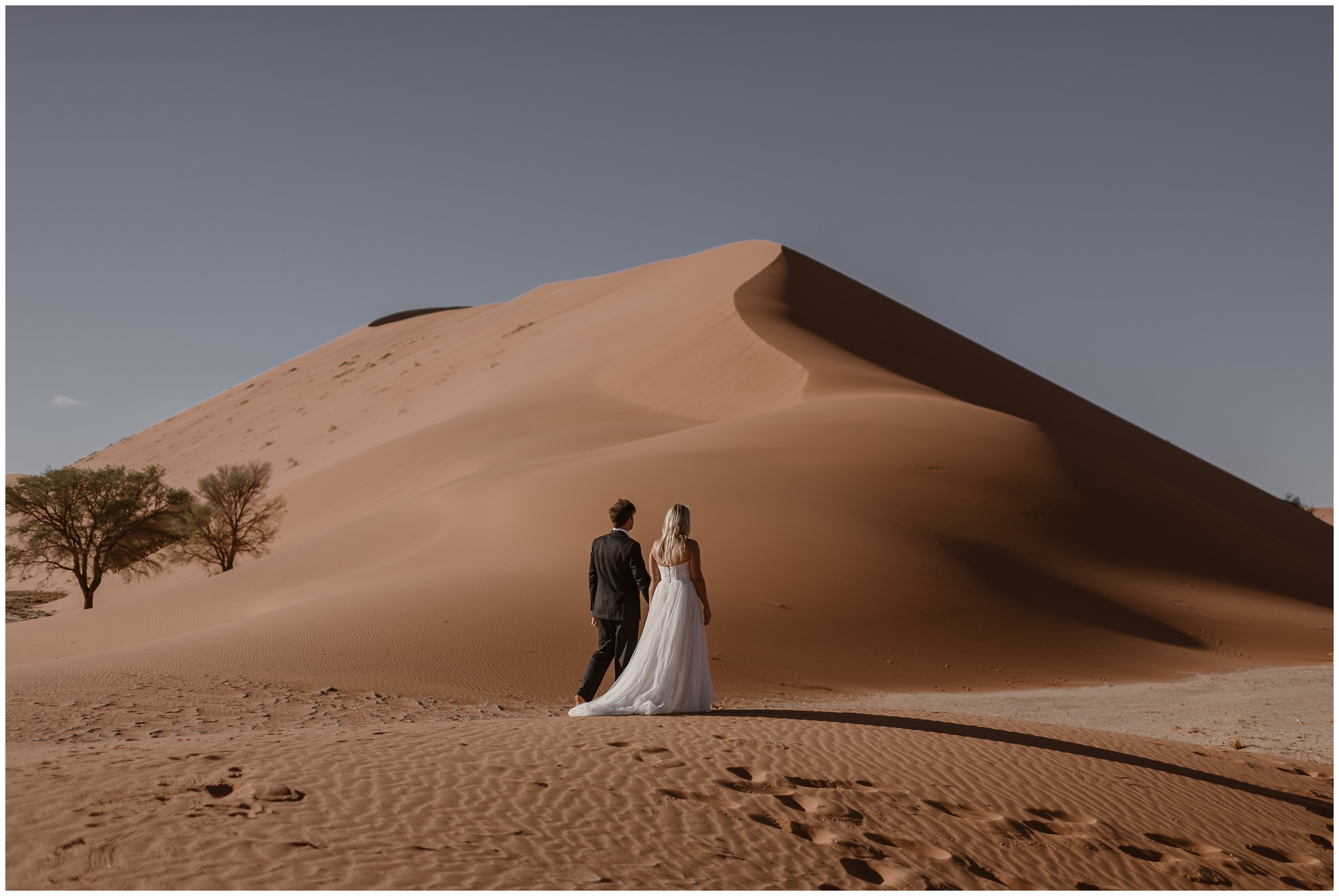 A bride and groom walk toward a gorgeous, enormous sand dune in the middle of the desert. The two are walking hand-in-hand toward their elopement ceremony location— these elopement photos were captured by elopement wedding photographer Adventure Instead.