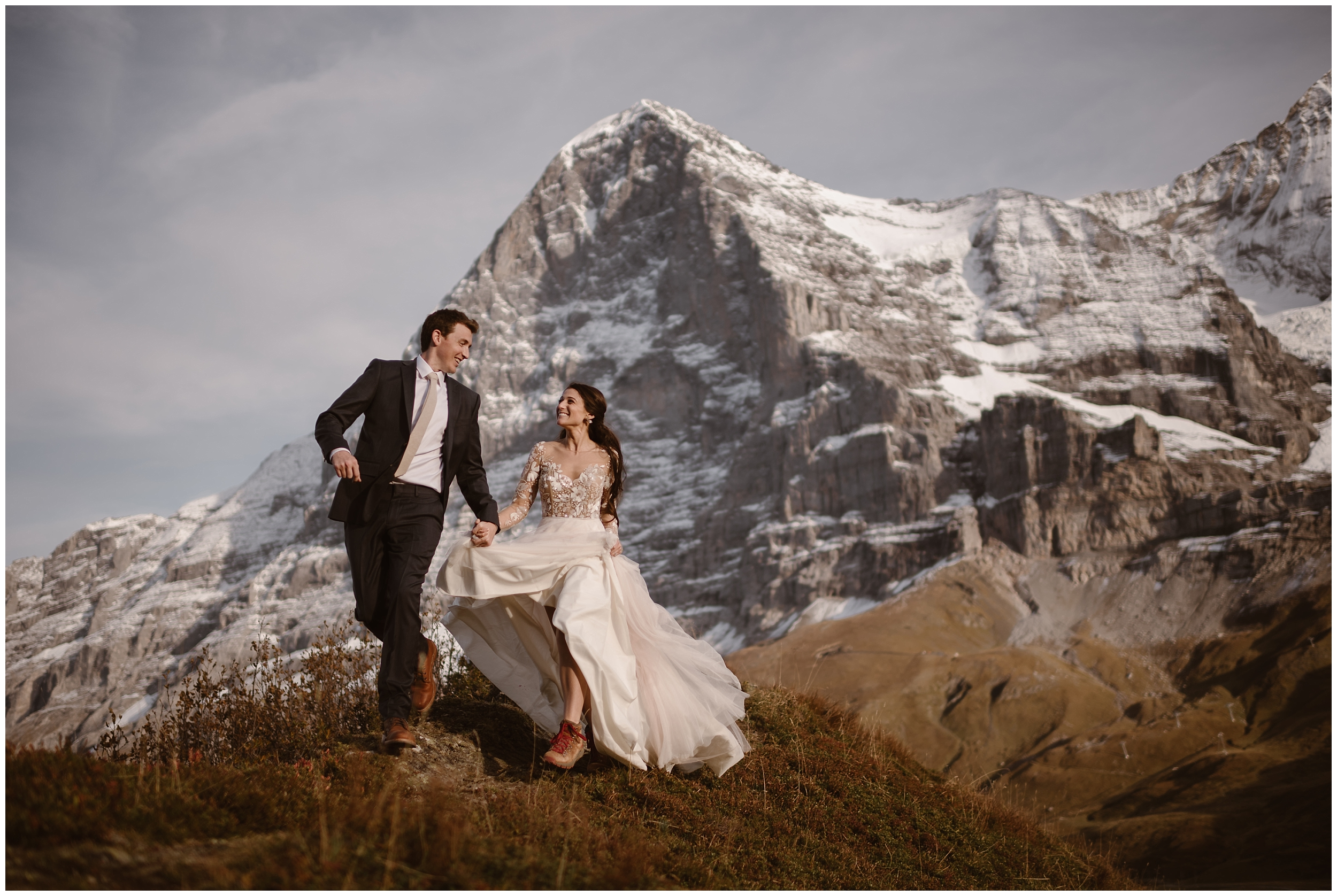 A bride and groom take hands in their wedding attire and run through an alpine mountain. Behind them, a giant, Switzerland peak reaches toward the sky. The couple included this elopement location as one of the best elopement ideas for their elopement wedding. These adventure elopement pictures were captured by elopement photographer Adventure Instead.