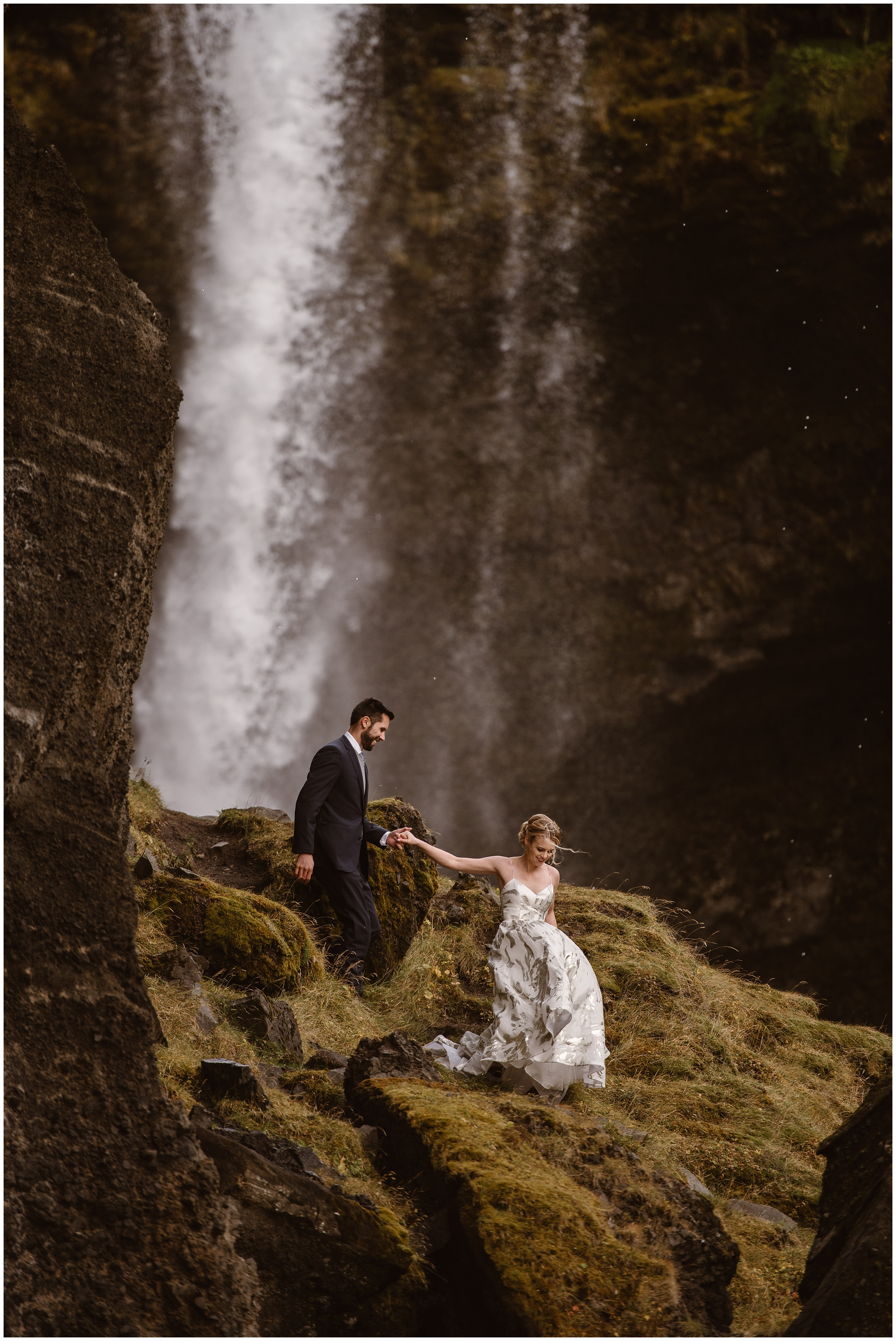 A brie leads her groom down a mossy path as a rushing waterfall powers forcefully behind them. Small wedding ideas like these make for the best elopement locations. Why elope, you might ask? You get to have your elopement wedding in a spot like this!