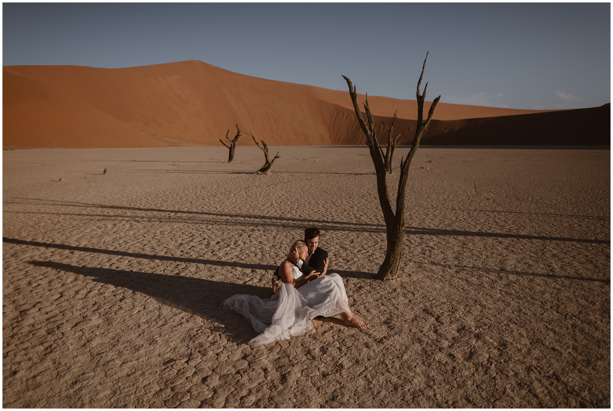 A couple sits on the desert ground in Africa, holding each other close. Behind them, giant orange sand dunes rise up toward the sky. When people ask what is an elopement wedding, we love to show them elopement photos like these—it's anything you want it to be. It's unique eloping ideas in destination elopement locations.