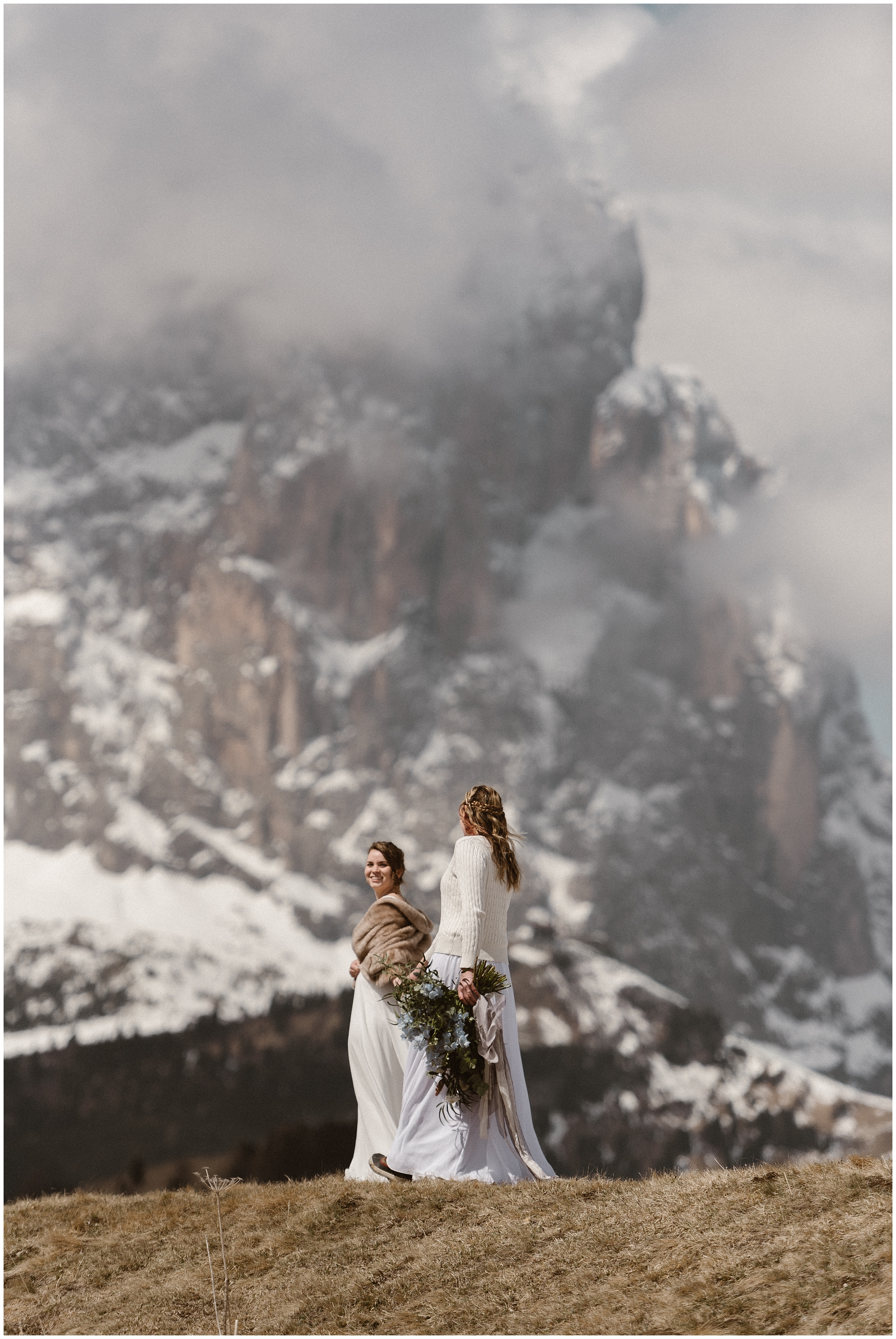 Two brides take hands in white wedding dresses (and with gorgeous bouquets) and walk toward a gorgeous, granite and snow-covered mountain peak. This is one of the best places to elope because of its gorgeous scenery.