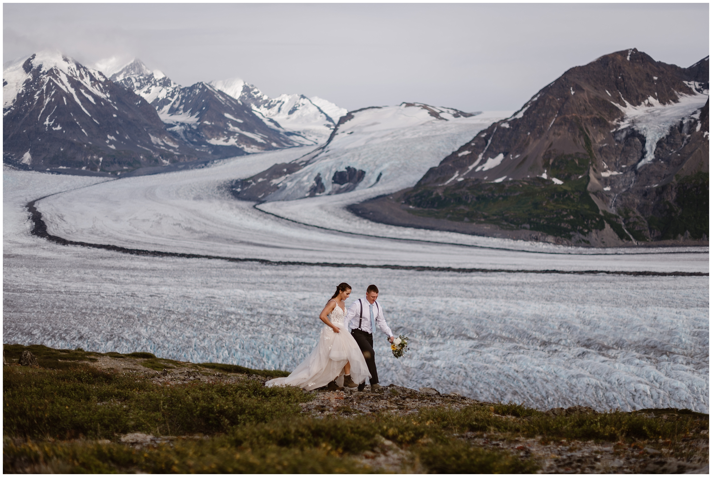 A bride and groom take hands and walk by a glacial lagoon in Alaska—a gorgeous spot for a destination elopement. These adventure elopement pictures were captured by Adventure Instead, an elopement photographer.