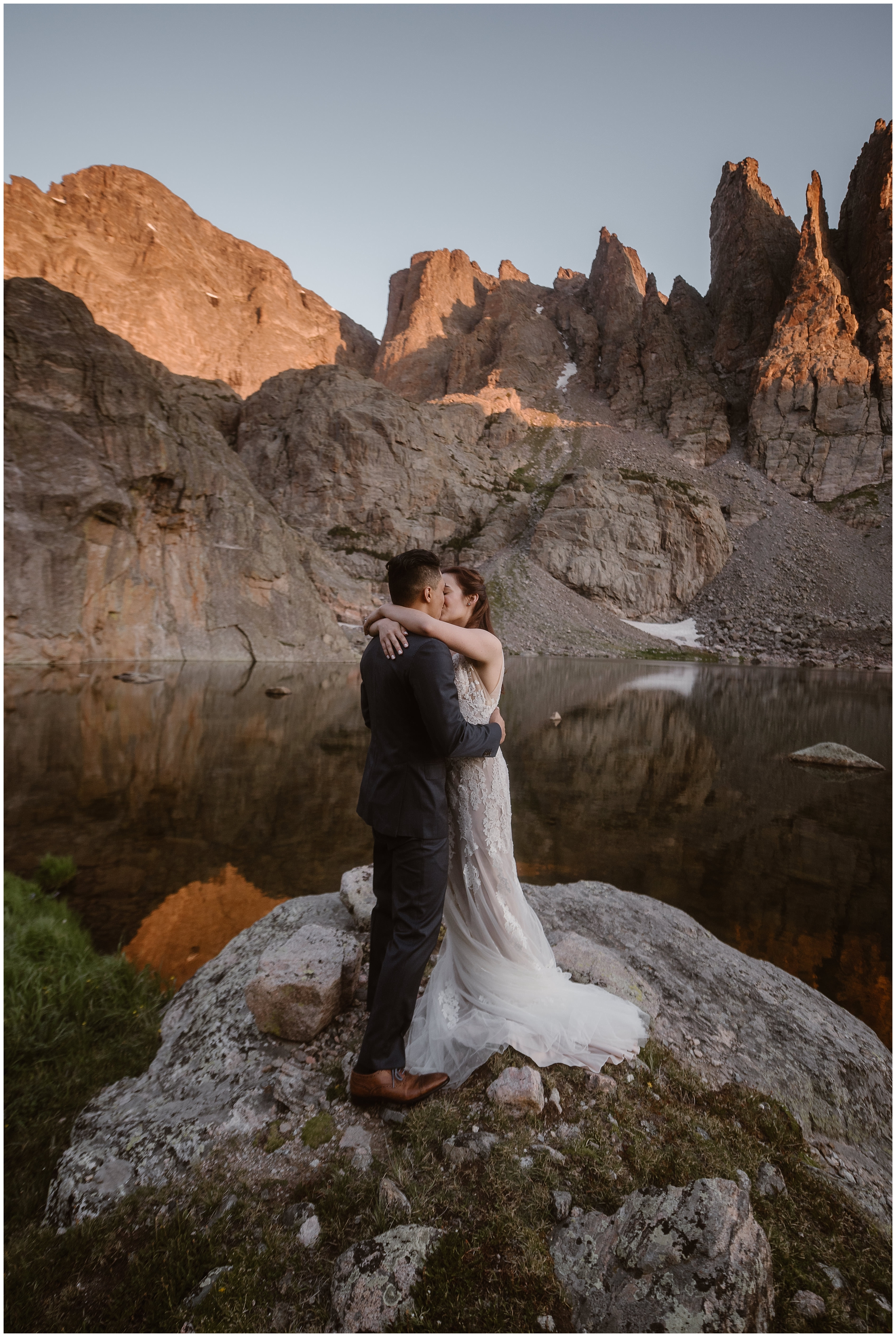A bride and groom embrace and kiss as they stand on a granite and mossy rock on the edge of an alpine lake. All around them, giant mountain crags peek up toward the sky. Eloping where and when you want are some of the best elopement ideas to consider for your small simple wedding.