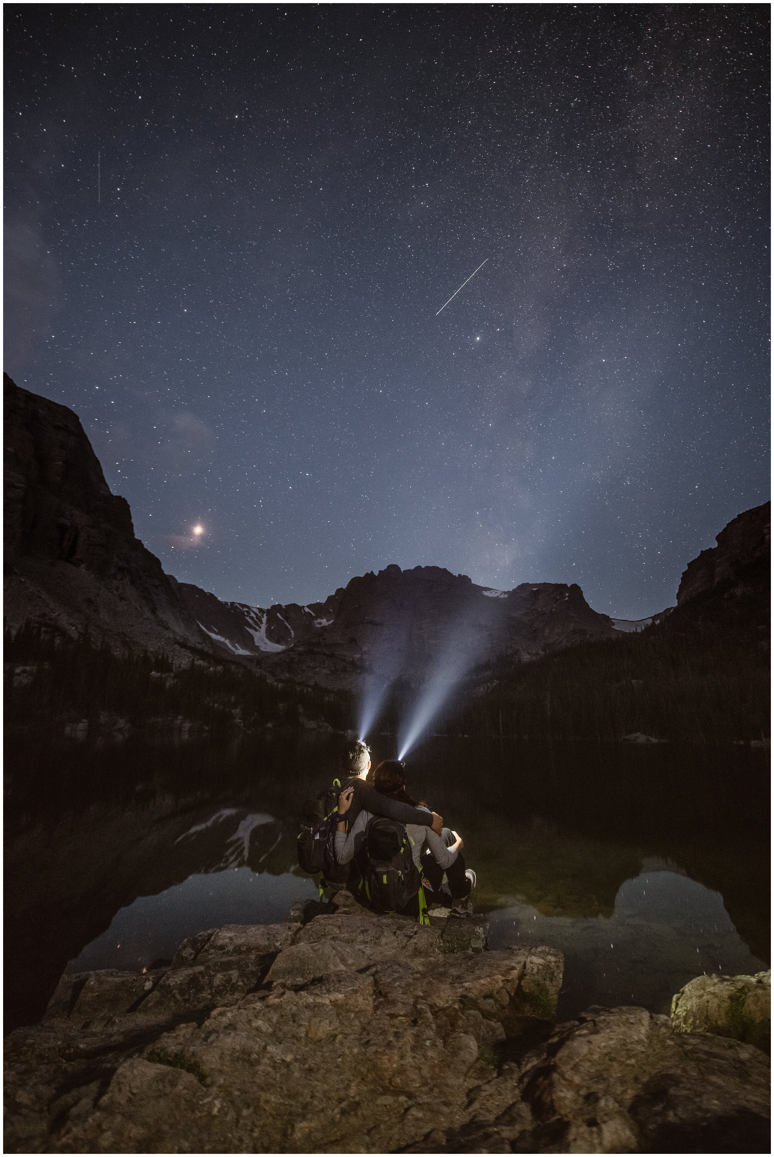 A bride and groom sit by a lake in the dark, the stars and their headlamps the only lights shining down on the scenery in front of them. Hiking up to your elopement ceremony location is one of the unique eloping ideas several couples want to include in their elopement wedding.