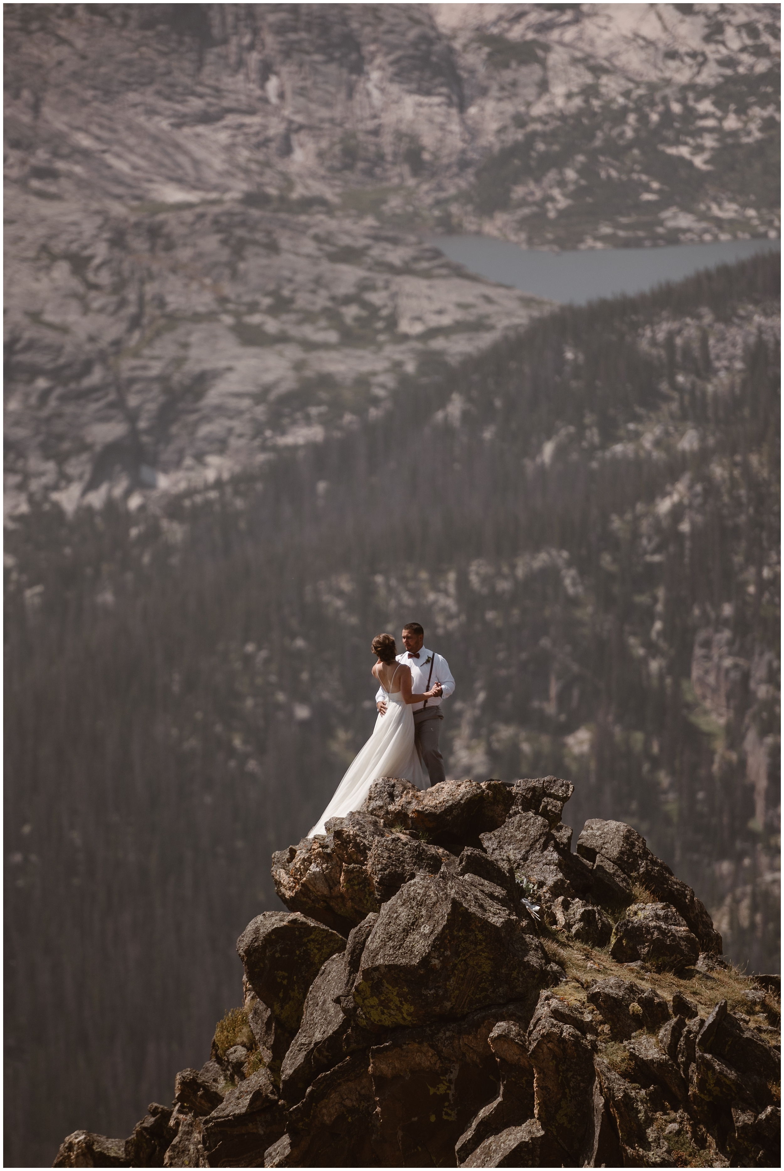 A bride and groom hold each other close as they stand at the top of a rocky mountain peak. Behind them, a forest full of tall, gorgeous pines is shown, as well as an alpine lake off in the distance.