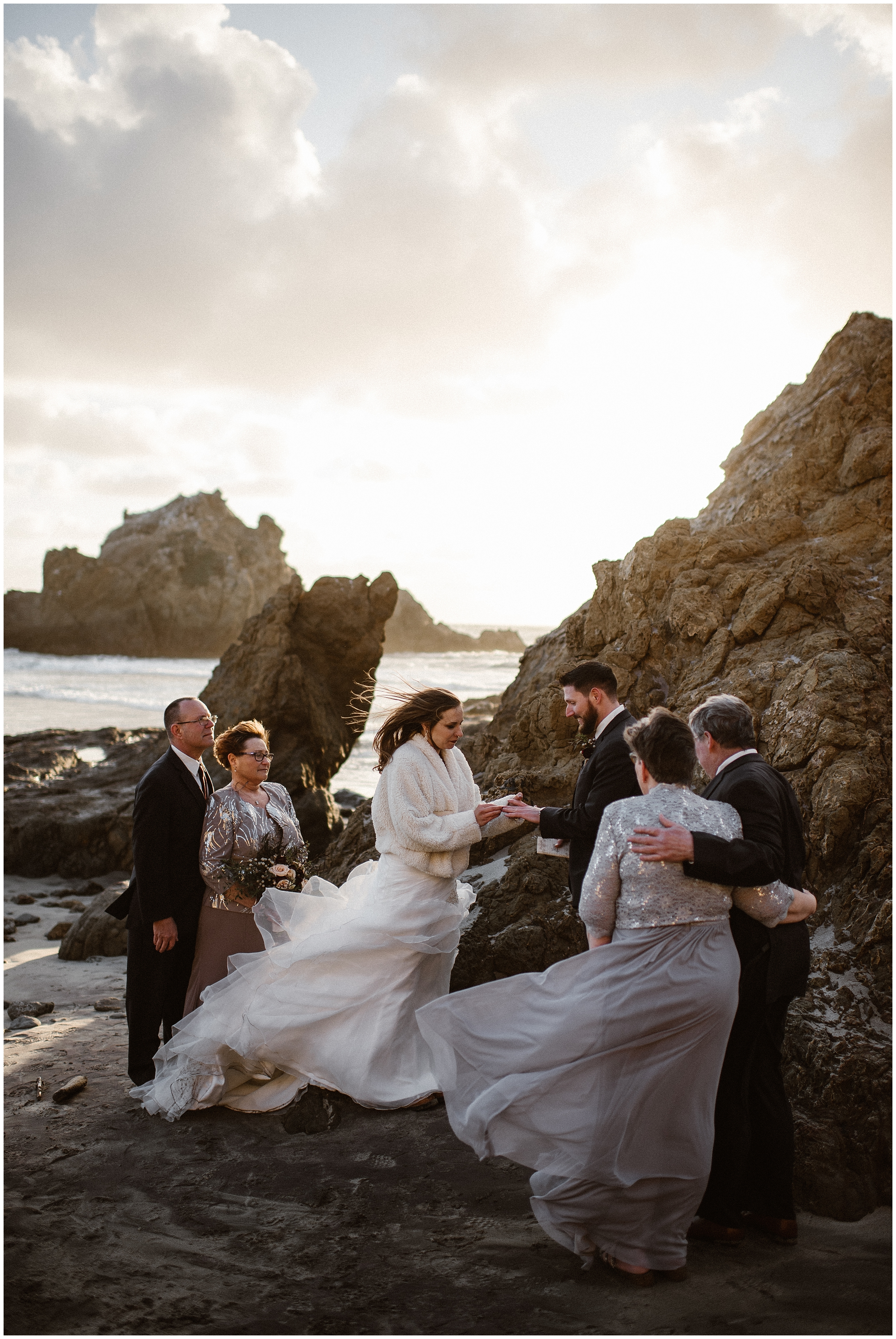 A bride and groom say their vows in front of their witnesses during their elopement ceremony. They're standing on a rocky, sandy beach on the Pacific Ocean. The bride, wearing a wedding dress and a white jacket, slips the wedding ring on her new husbands finger. Eloping with family is a great way to ensure you have the witnesses you need at your ceremony.