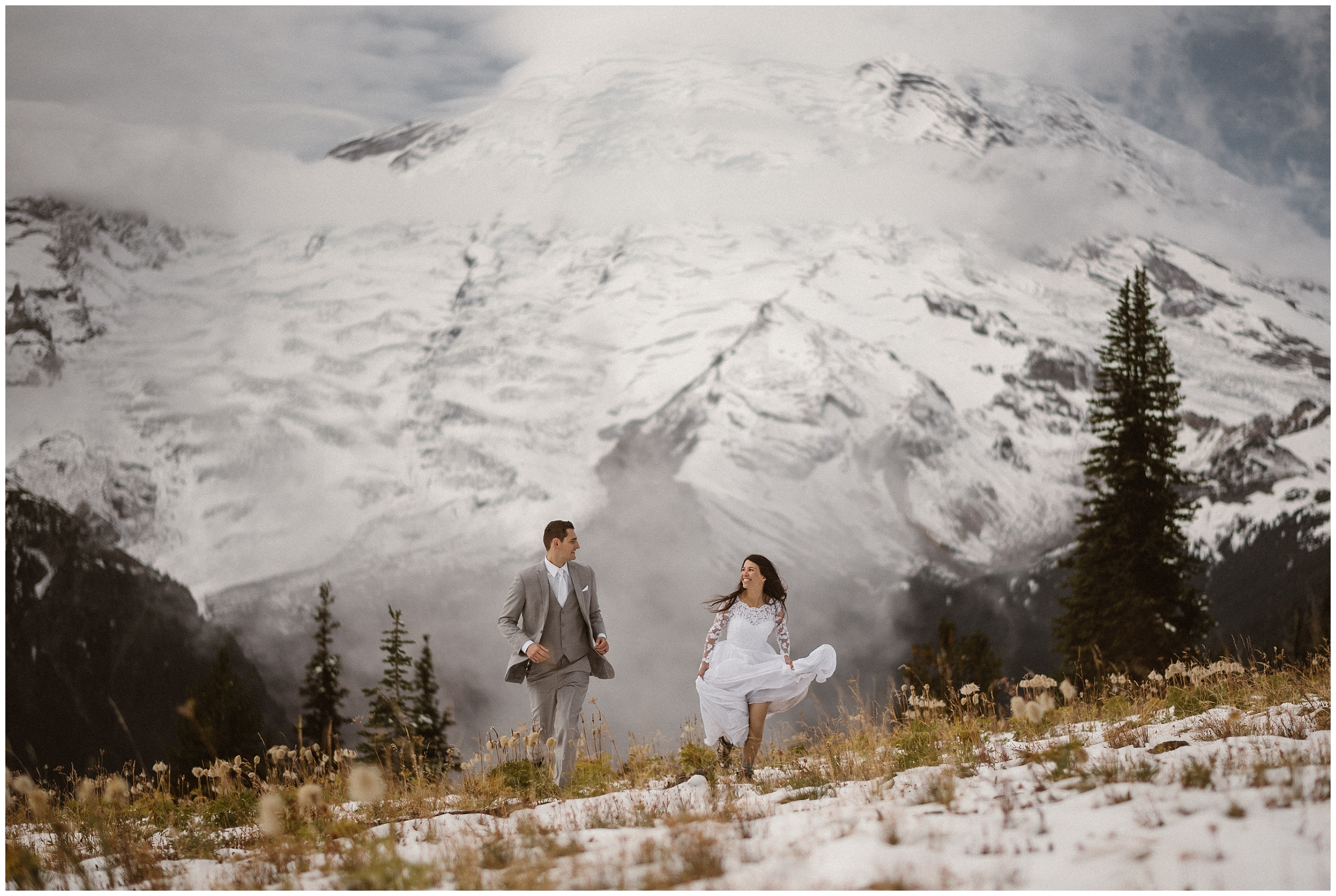 A bride and groom run through a snowy, alpine meadow in their wedding attire. The bride, gathering up her white wedding dress in her hands to reveal her hiking boots underneath, looks at the groom, running alongside her in a light grey suit. Behind them, an enormous, snowy mountain is looming.