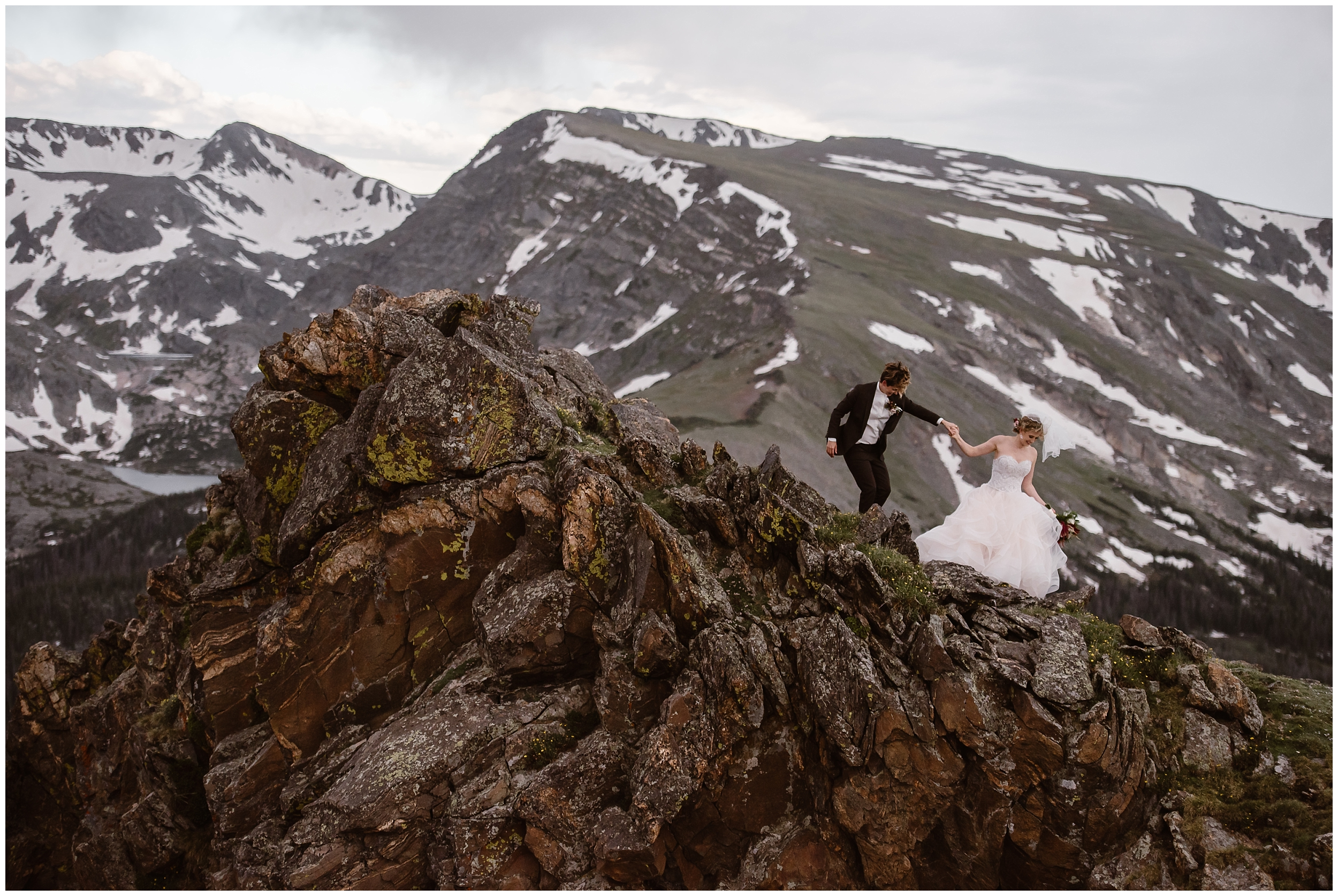 A bride and her partner hold hands as they traipse down a rocky mountainside together. Her partner, in a black suit, holds her hand as she hold up her wedding dress. Snowy mountains can be seen in the background.