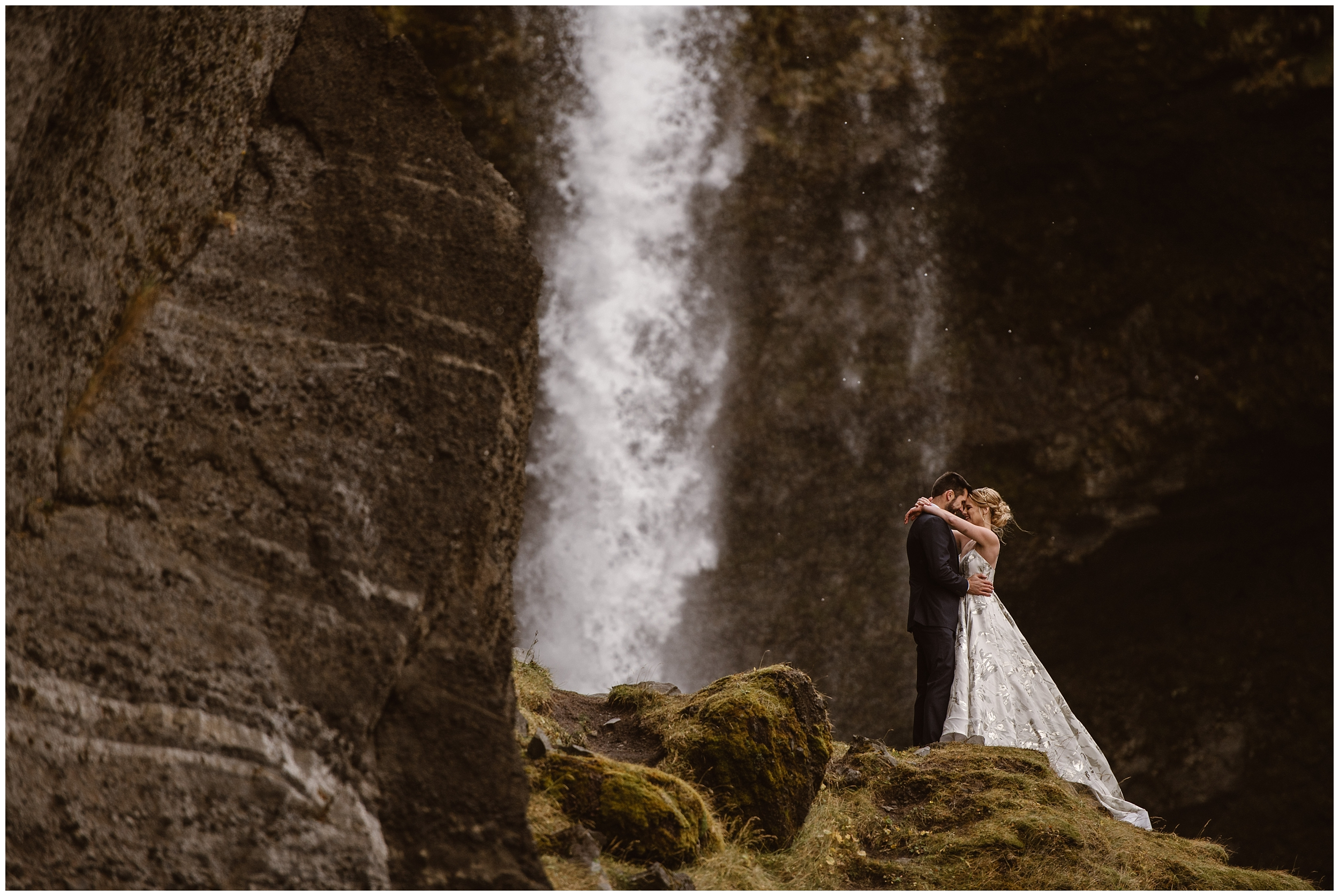 A bride and groom stand on a mossy, rocky platform as a powerful waterfall rushes behind them. They hold each other close for their adventure elopement photos which were captured by Adventure Instead.