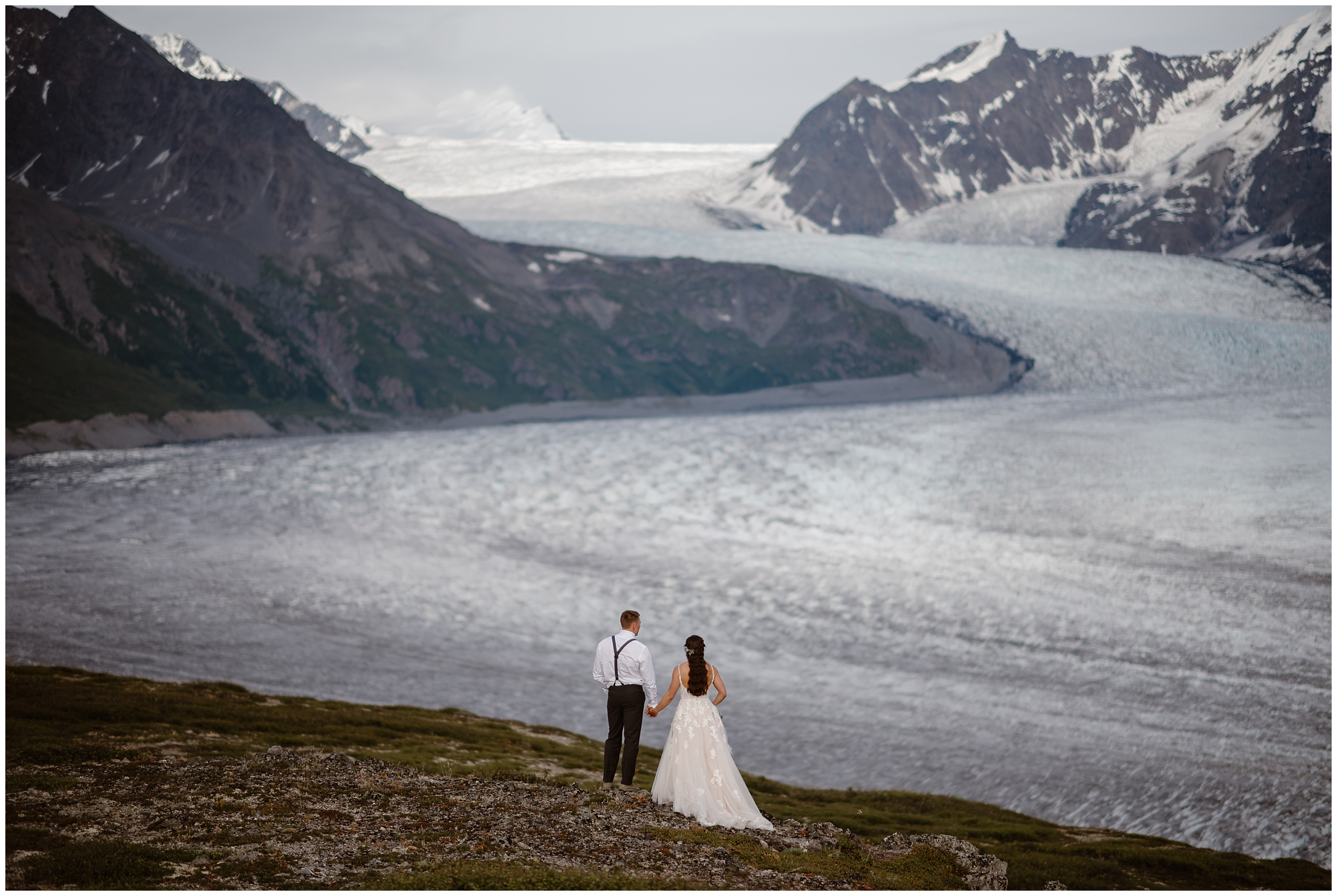 A bride and groom hold hands and stand with their backs to the camera as they look on to an enormous, beautiful glacier field in the Alaska wilderness. This bride and groom included a helicopter in their unique eloping ideas for their elopement ceremony.