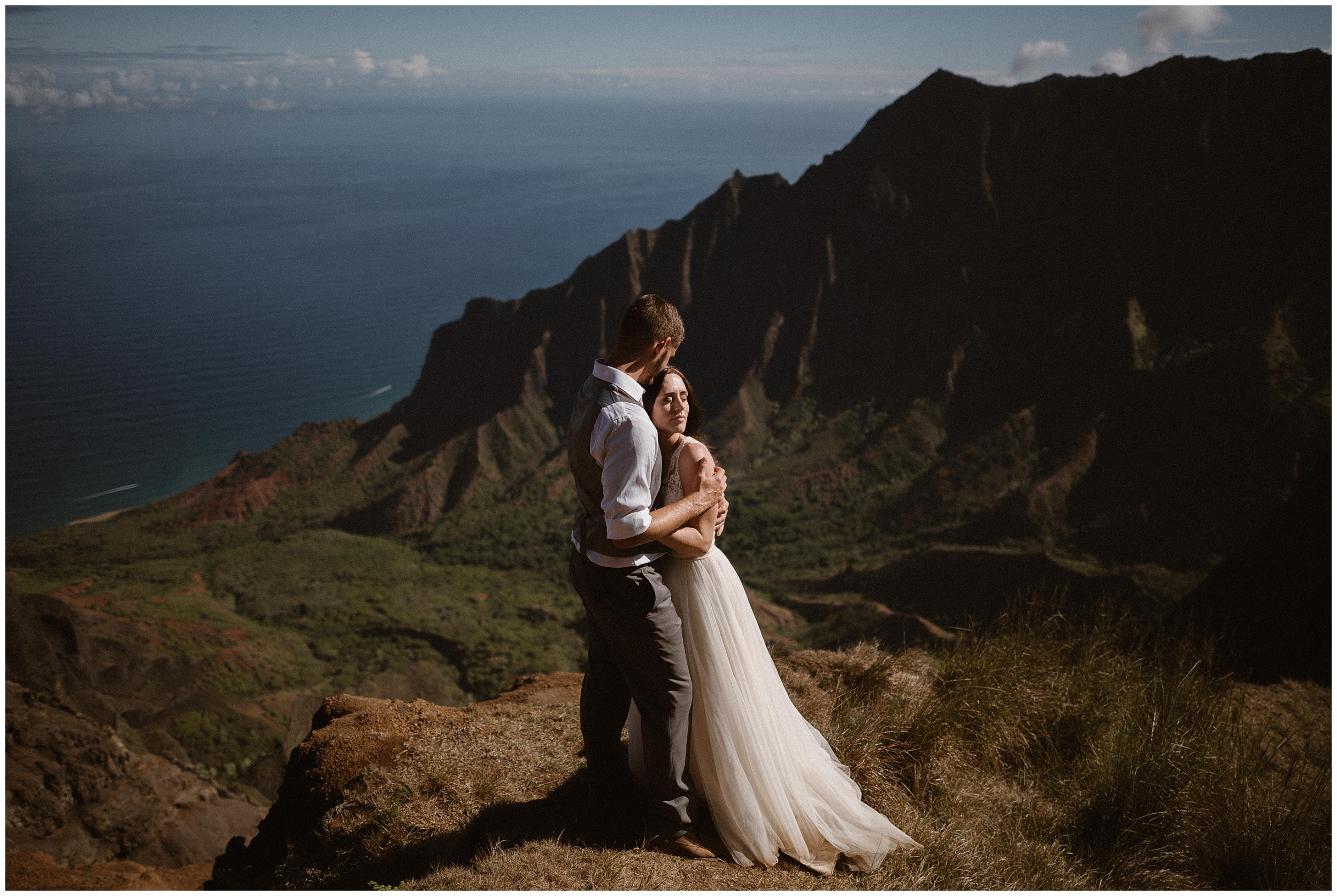 A bride and groom hold each other close while they stand at the top of a cliff overlooking a beautiful Hawaiian beach. These elopement photos were captured by Adventure Instead, a destination elopement photographer.