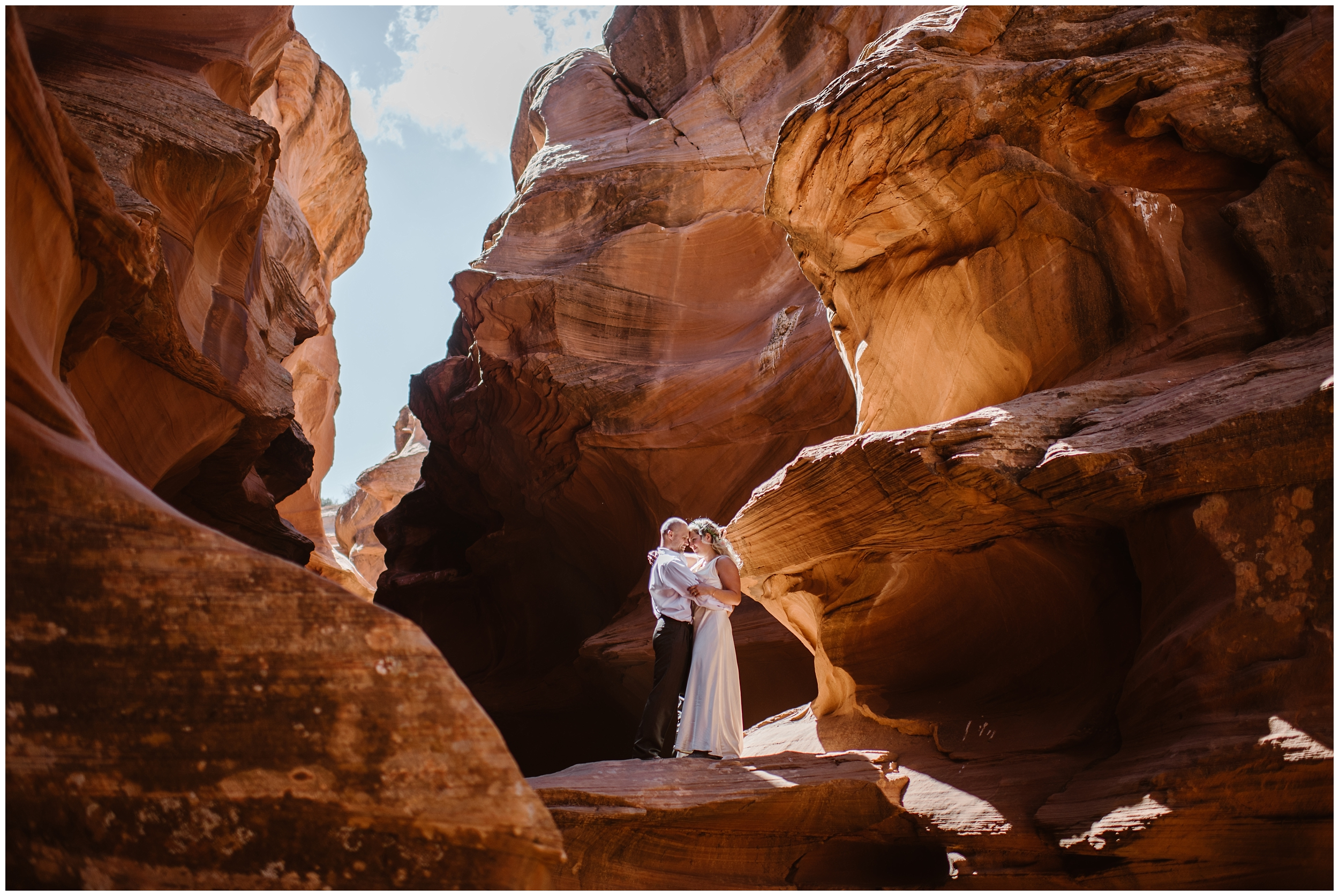 A couple holds each other close in a slot canyon in the Arizona wilderness. These adventure elopement photos were captured by Adventure Instead, an elopement photographer.