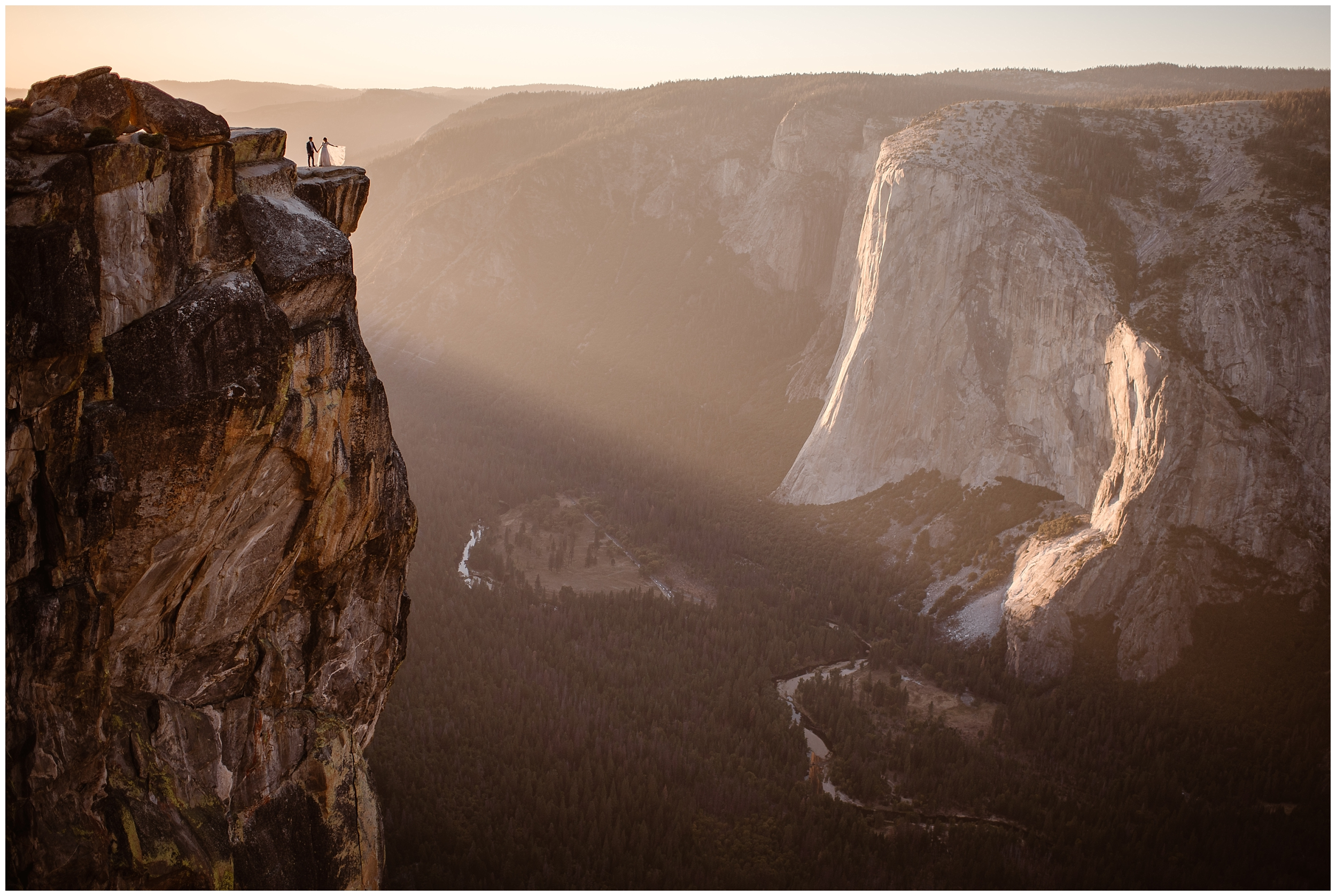 In the distance, a bride and groom can be seen standing on the edge of a cliff in Yosemite National Park during golden hour. These elopement photos are captured by Adventure Instead, an elopement photographer.