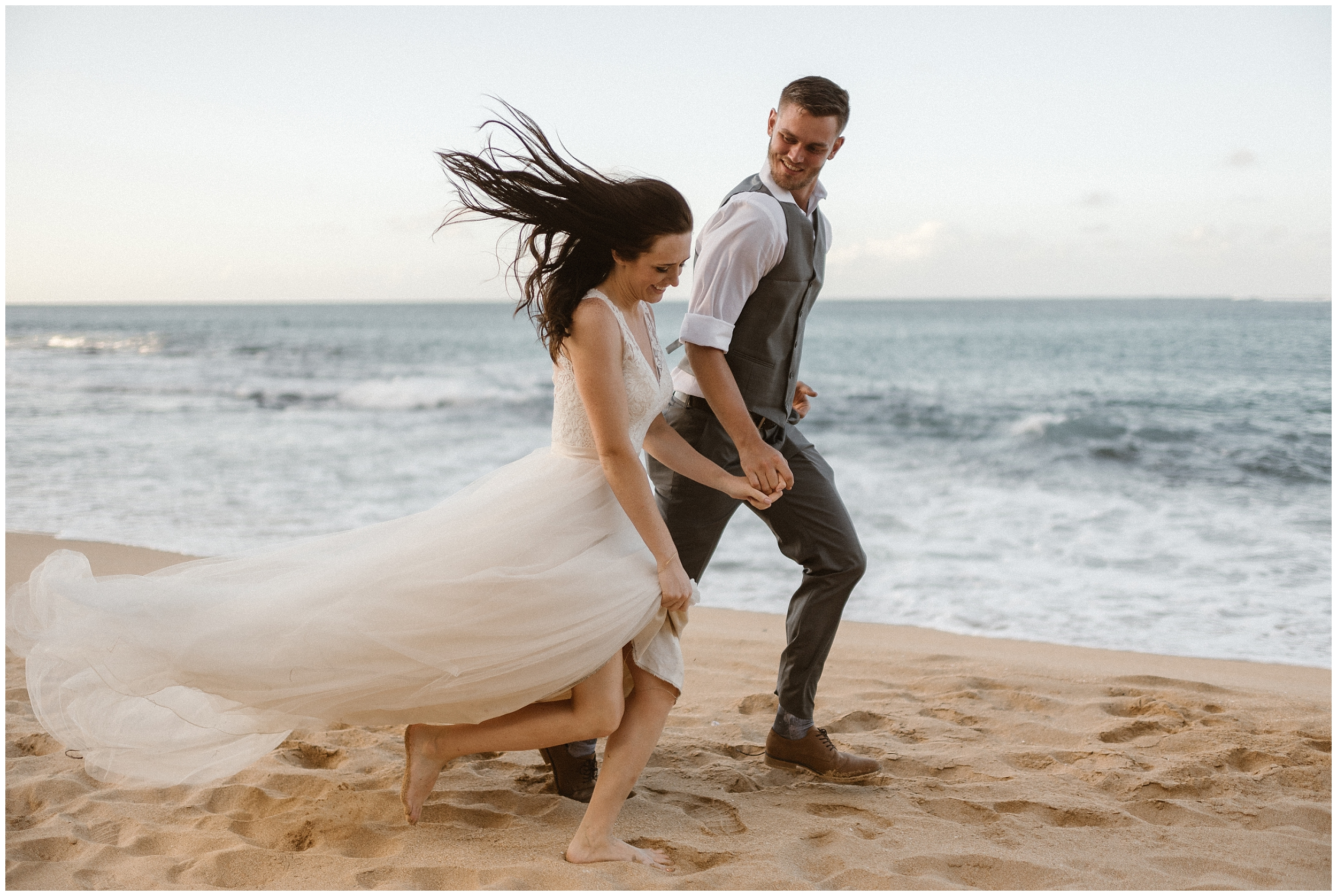 A bride and groom, in their wedding attire, walk hand-in-hand down a beautiful beach in the United States. The couple wanted to include this unique eloping idea into their small simple wedding.