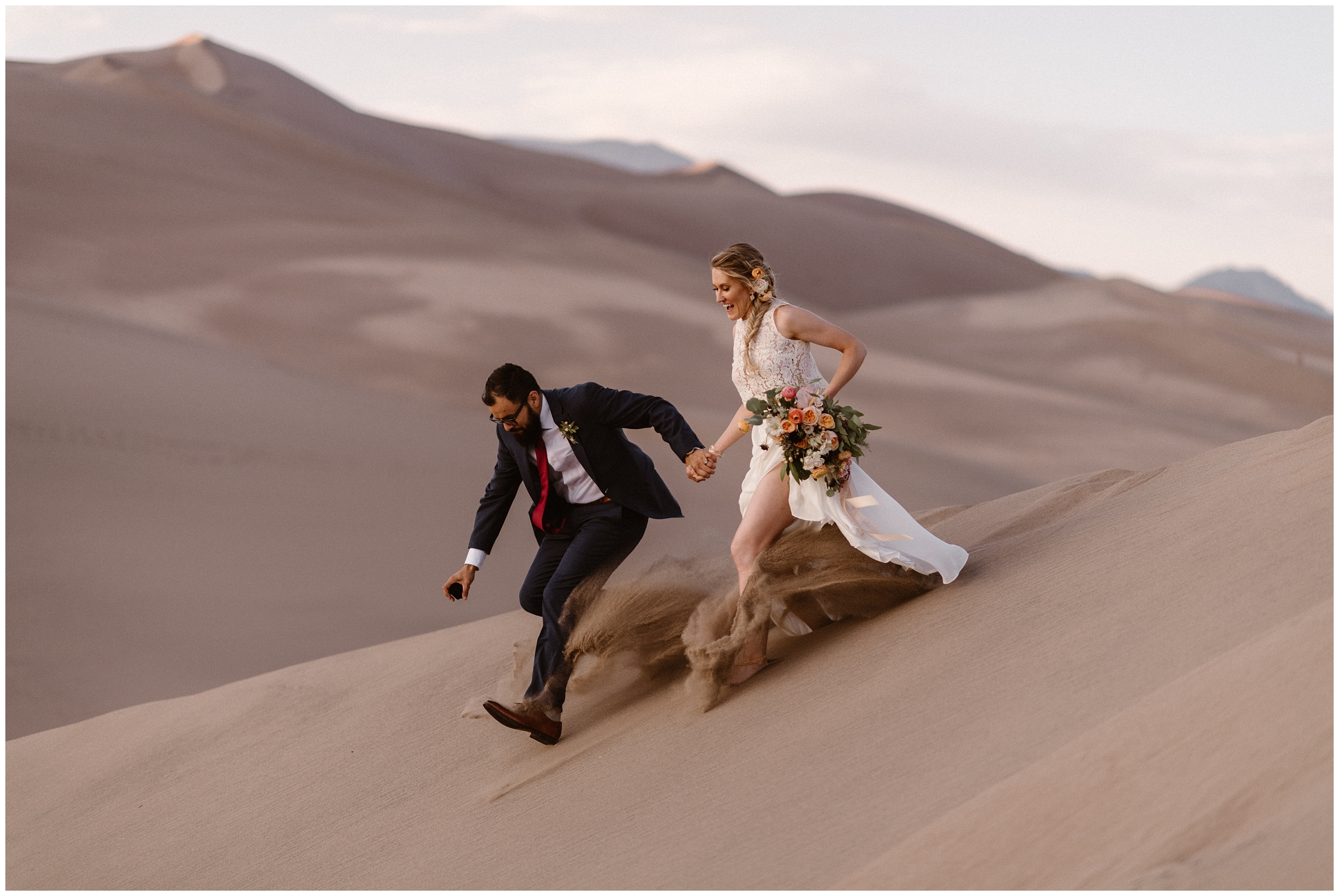 A bride and groom slip and slide down a sand dune in Colorado's Great Sand Dunes National Park. Decked out in their wedding attire, they take hands and run down the dune together. These adventure elopement photos were captured by Adventure Instead, elopement wedding photographers.