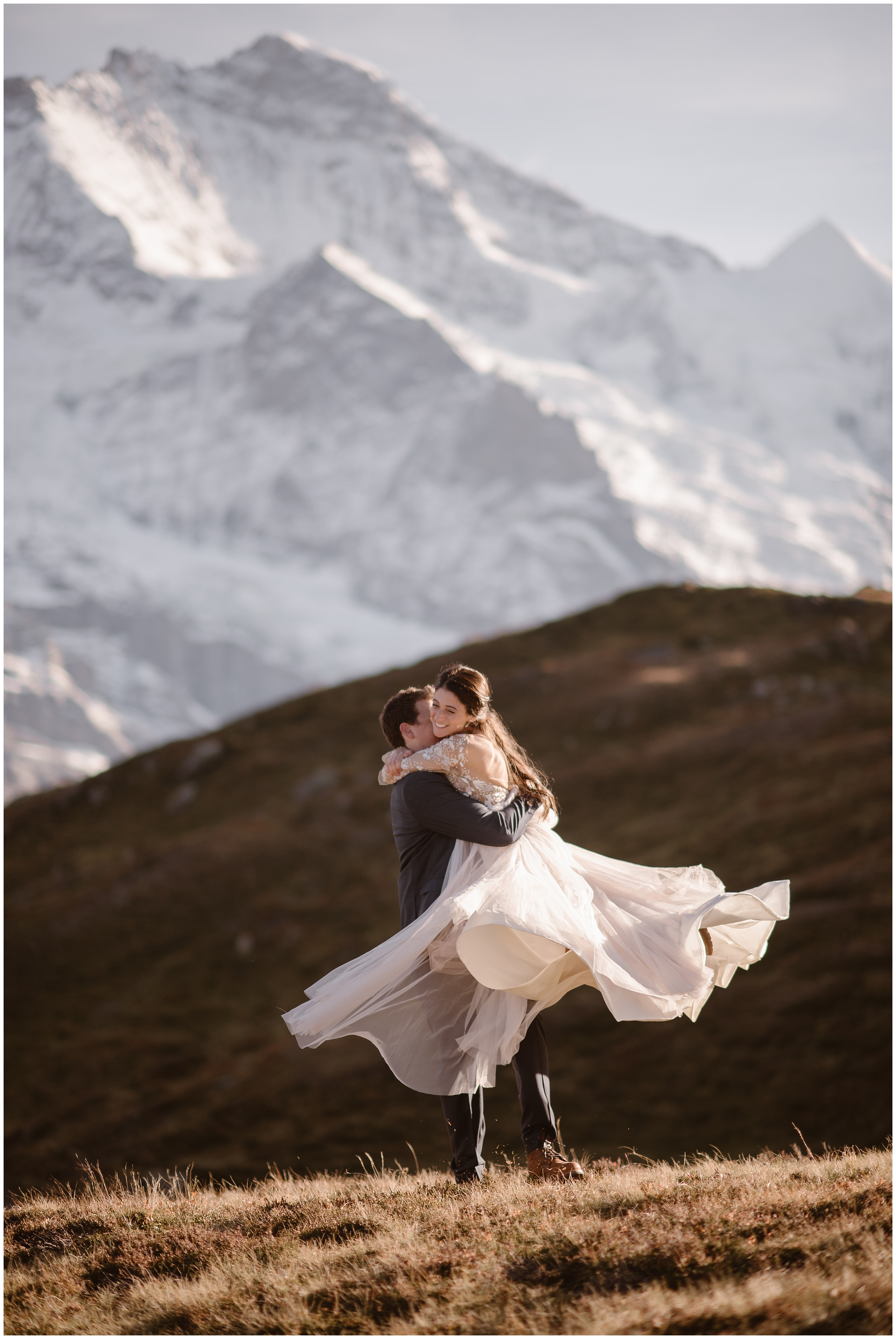 A bride and groom spin around outside on their wedding day in Switzerland in a photo captured by adventure elopement photographer Adventure Instead. Behind them, giant, snow-capped mountains can be seen.