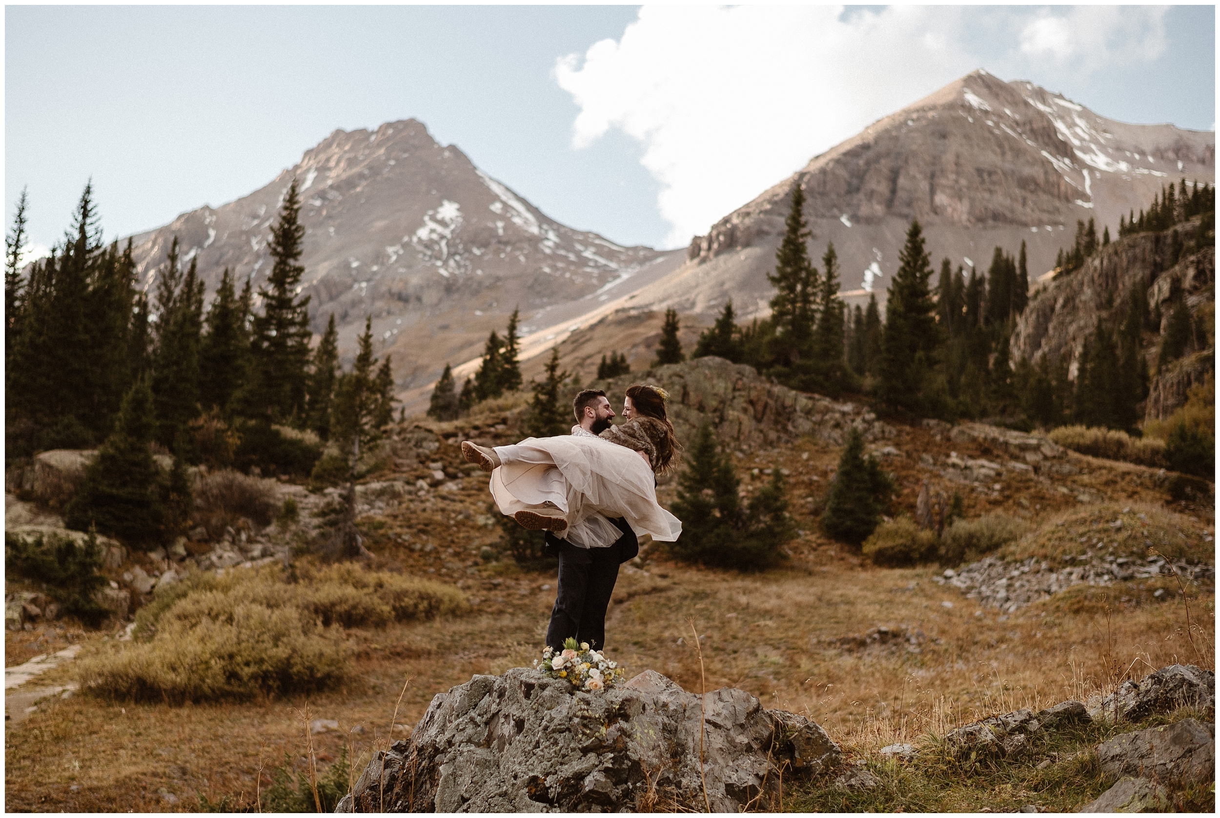 A groom sweeps his bride off her feet in the middle of a beautiful, mountain-lined forest. The dark green trees reach up toward the sky and the mountain peaks in the back are covered in snow — these unique eloping ideas (like having your destination elopement wherever you want) are the key benefits of eloping.
