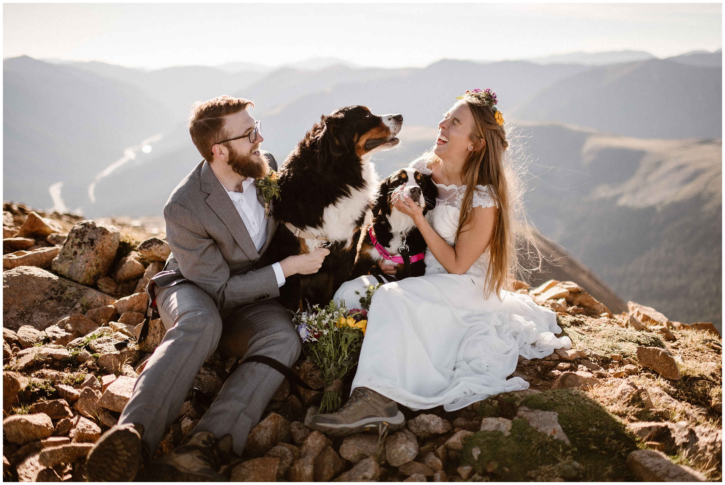 A couple and their two dogs cuddle up at the top of a mountain peak and pose for elopement pictures. Eloping with dogs is one of the unique eloping ideas you can include in your all day elopement!