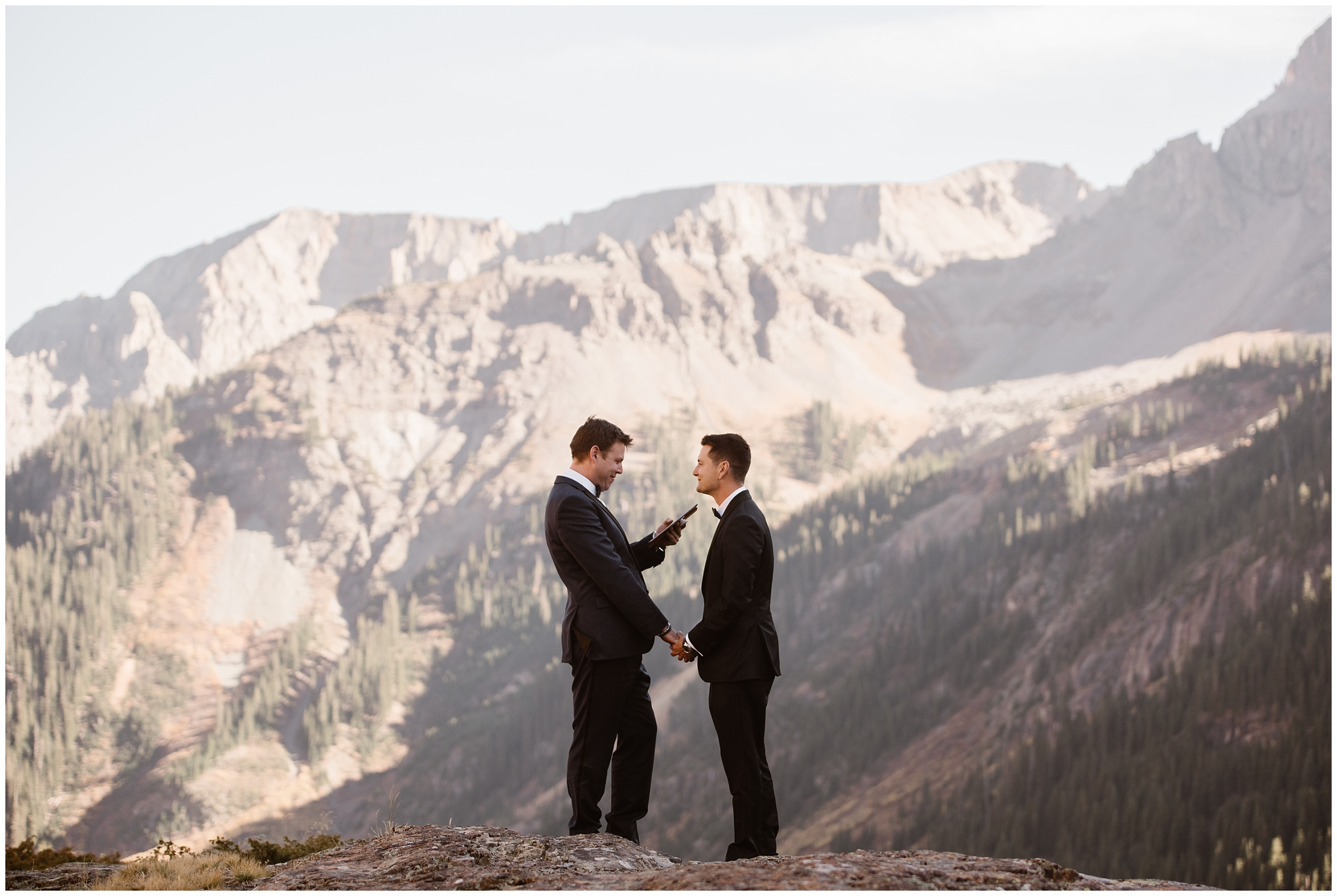 Brian and Ernie take each others hands during their elopement ceremon and read their vows to each other privately. Behind them, the San Juan moutnain range rises toward the sky and the sun casts a golden glow on the trees and moutnains.