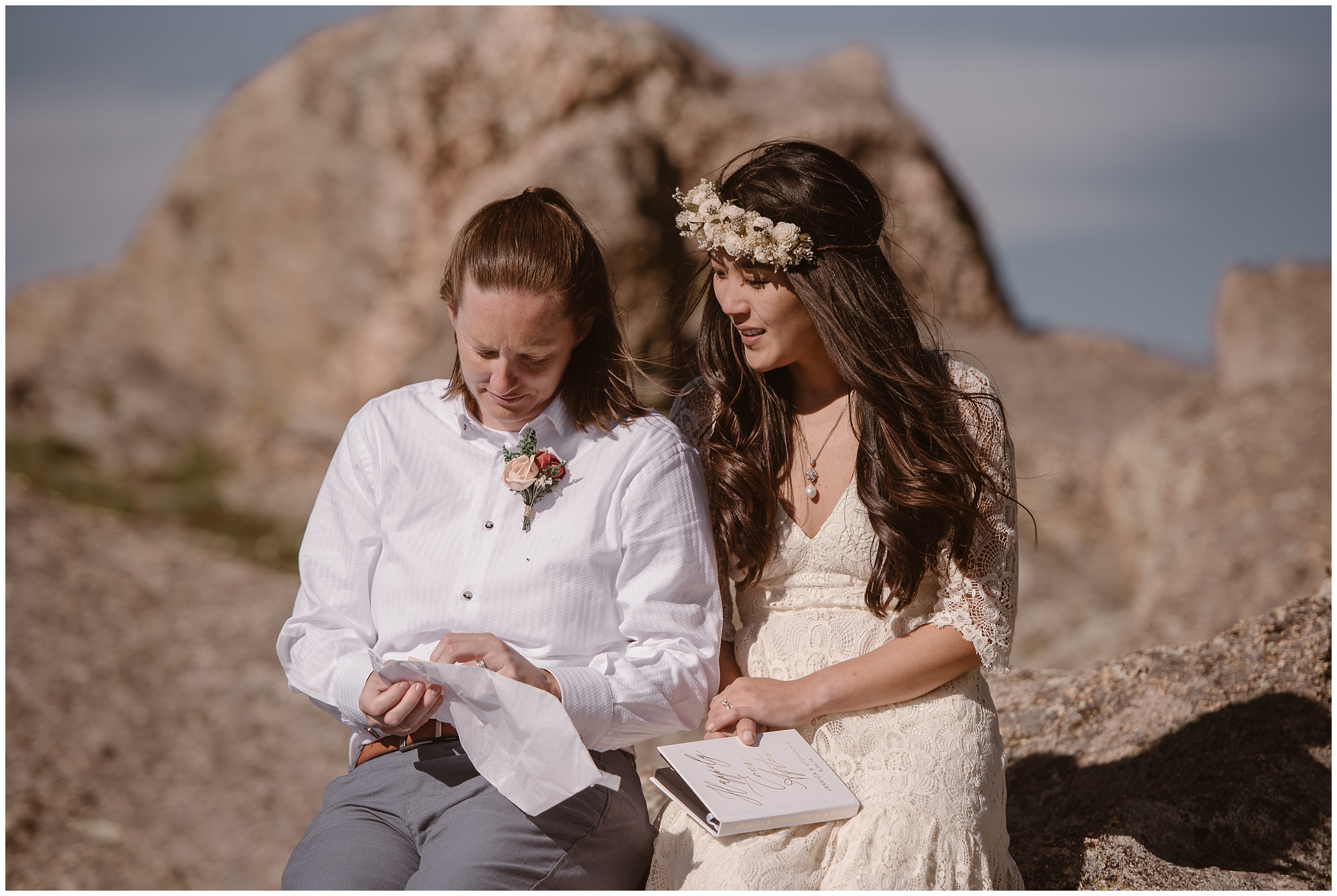 A couple sits next to each other, holding letters from friends and family and reading them during their party after eloping. This type of elopement wedding was a just us day, but the couple still chose to include their family in their elopement in a unique way.