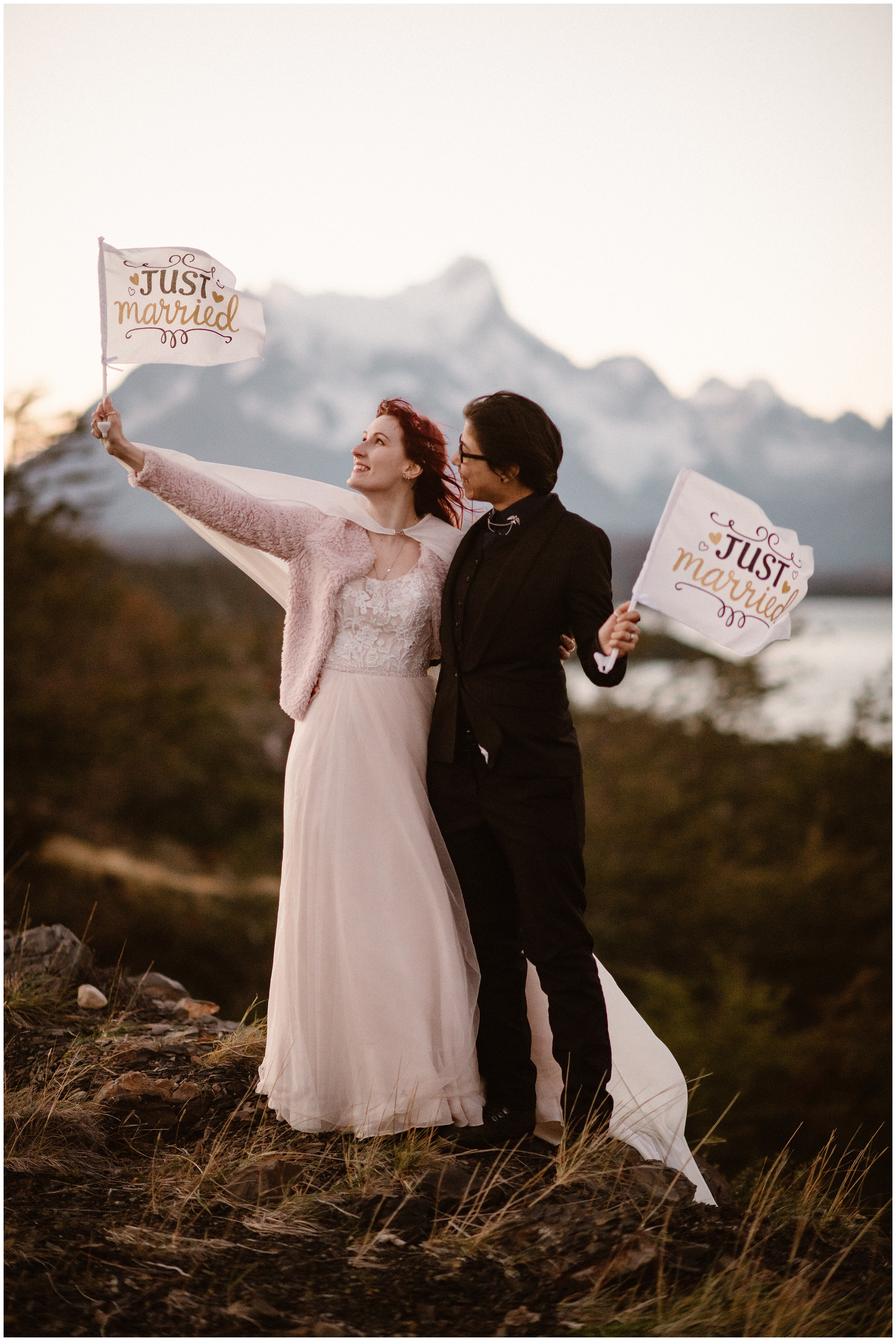 """Two young brides hold each other close as they fly two """"just married"""" flags during their Patagonia elopement ceremony. These adventure elopement photographs were captured by Adventure Instead, an elopement photographer."""