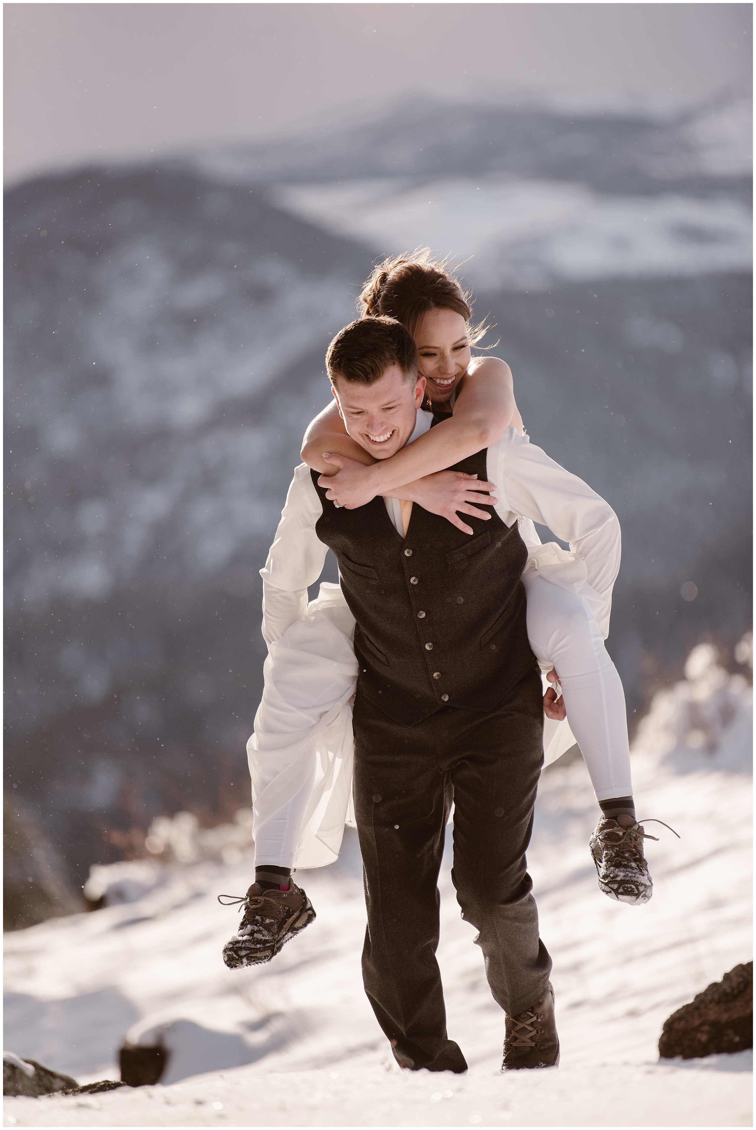 A bride rides piggyback on her groom as they hike through the snow during their Colorado mountain wedding ceremony. These adventure elopement pictures were captured by Adventure Instead, an elopement photographer.