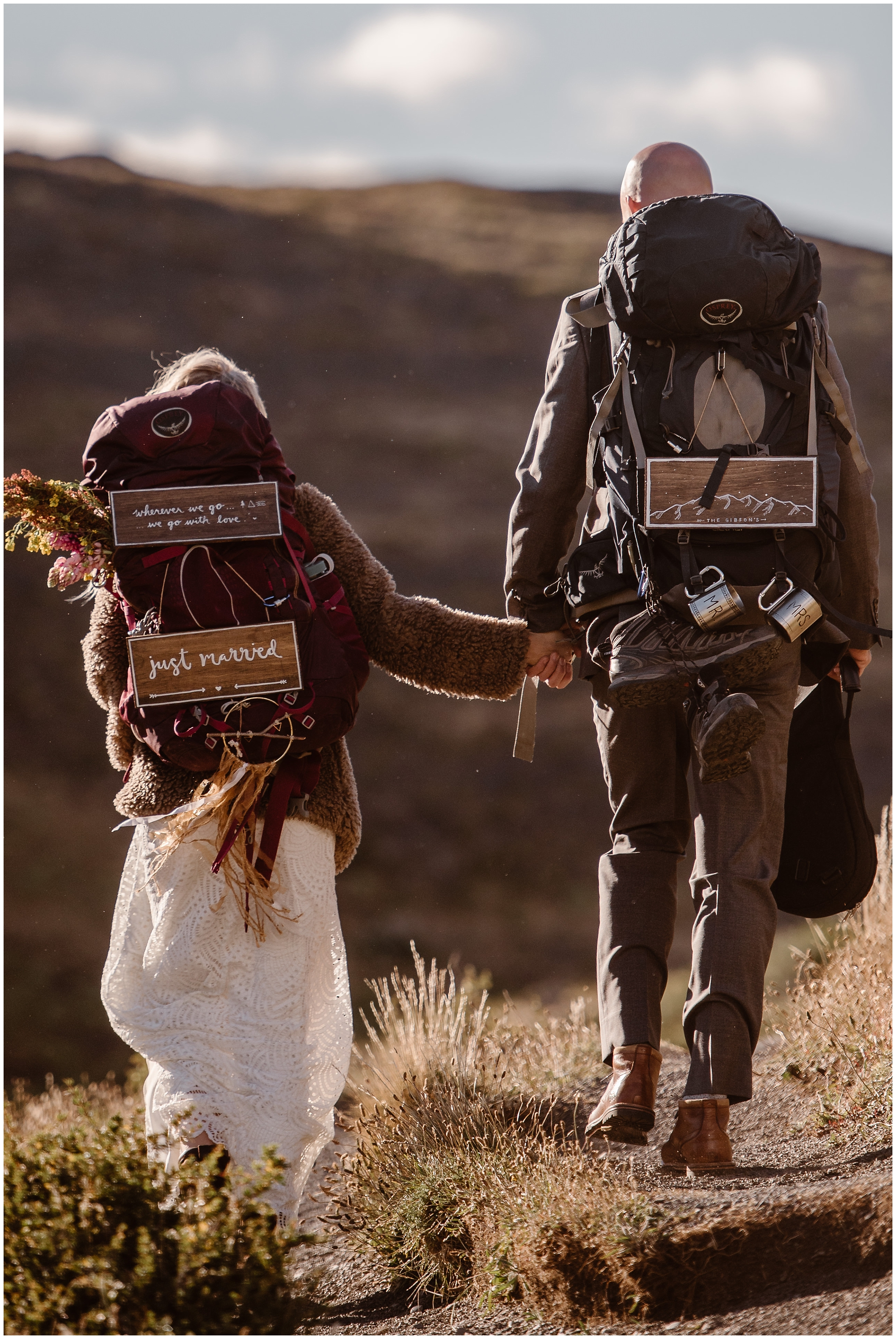 A couple hikes away hand in hand during their Patagonia elopement ceremony. On their backpacks, they each have signs that say just married. This hiking elopement was a simpe wedding idea that they wanted to incorporate in their small simple wedding.