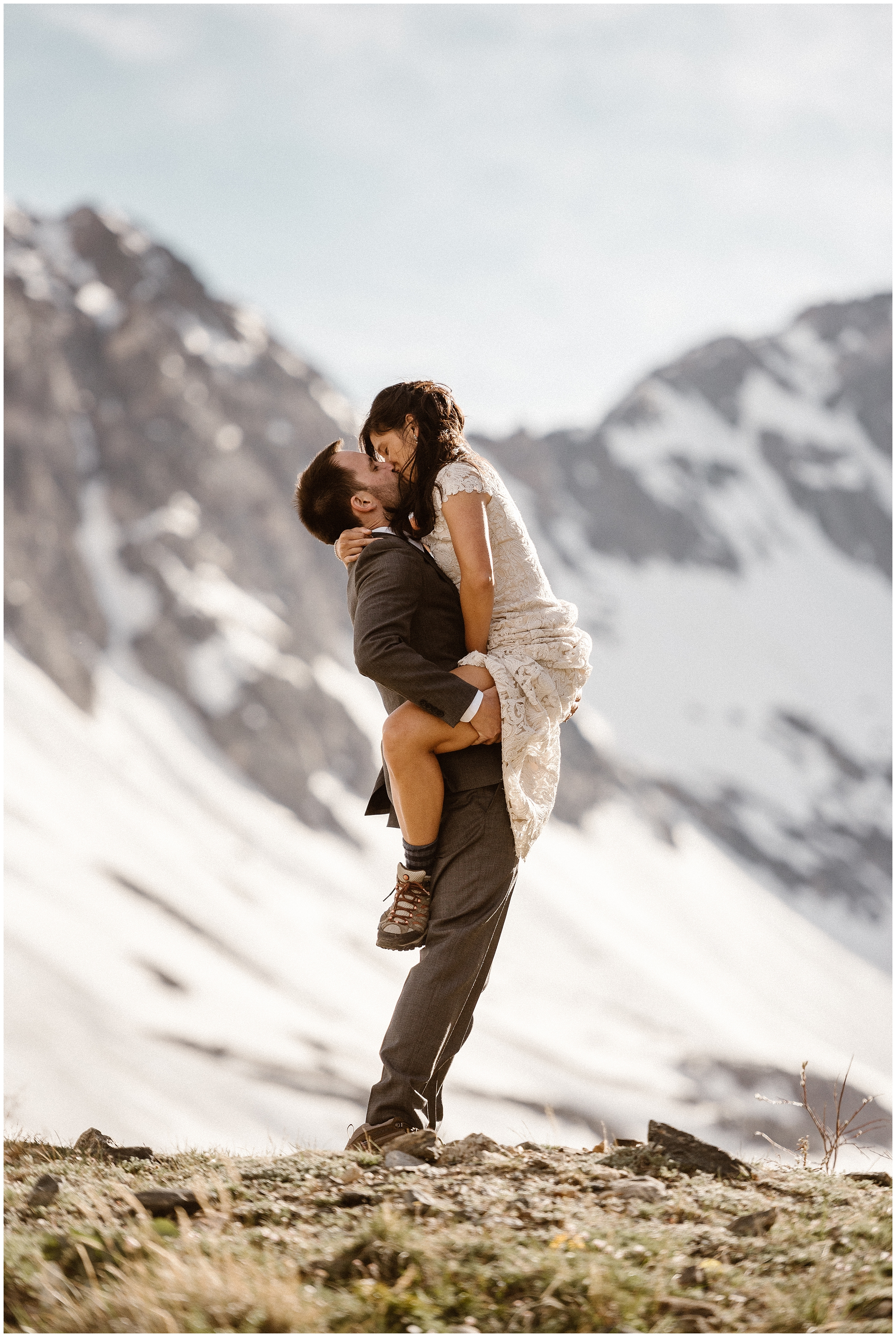 A groom holds up his bride in the mountains as they kiss and embrace after their elopement ceremony. When people ask, how do you elope, this is what it looks like — doing exactly what you want on your wedding day and taking the elopement photos you want to take.