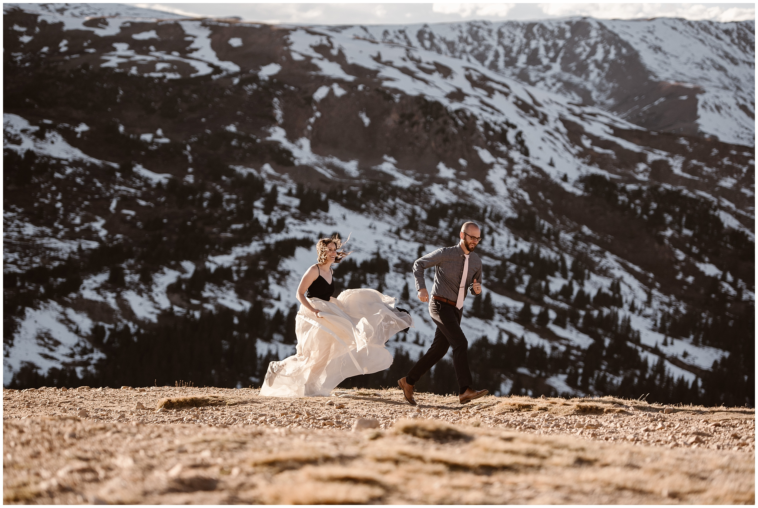 A young couple runs through an alpine meadow together in wedding attire. This simple wedding idea allowed this couple to elope in the destination they wanted to and have the elopement ceremony they wanted.