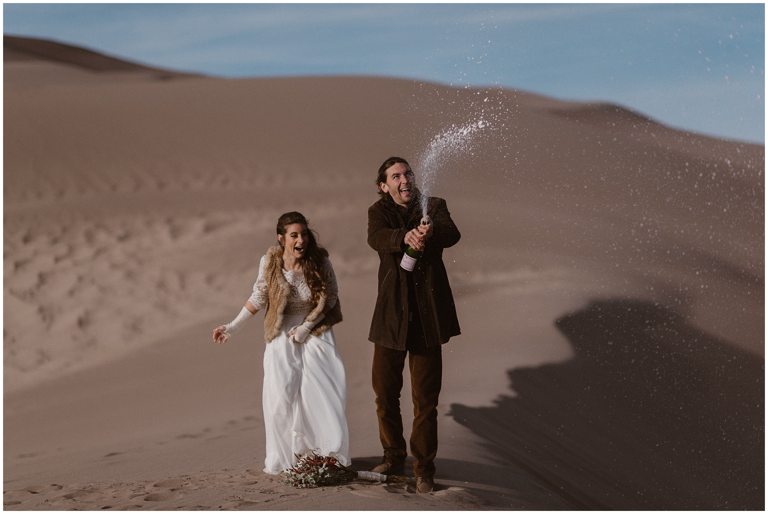 A bride and groom stand in the sand dunes as they pop celebratory champagne together. This unique eloping ceremony was a unique way for the bride and groom to elope in the location they want to. What's elope mean? Doing exactly what you want — just like this couple.