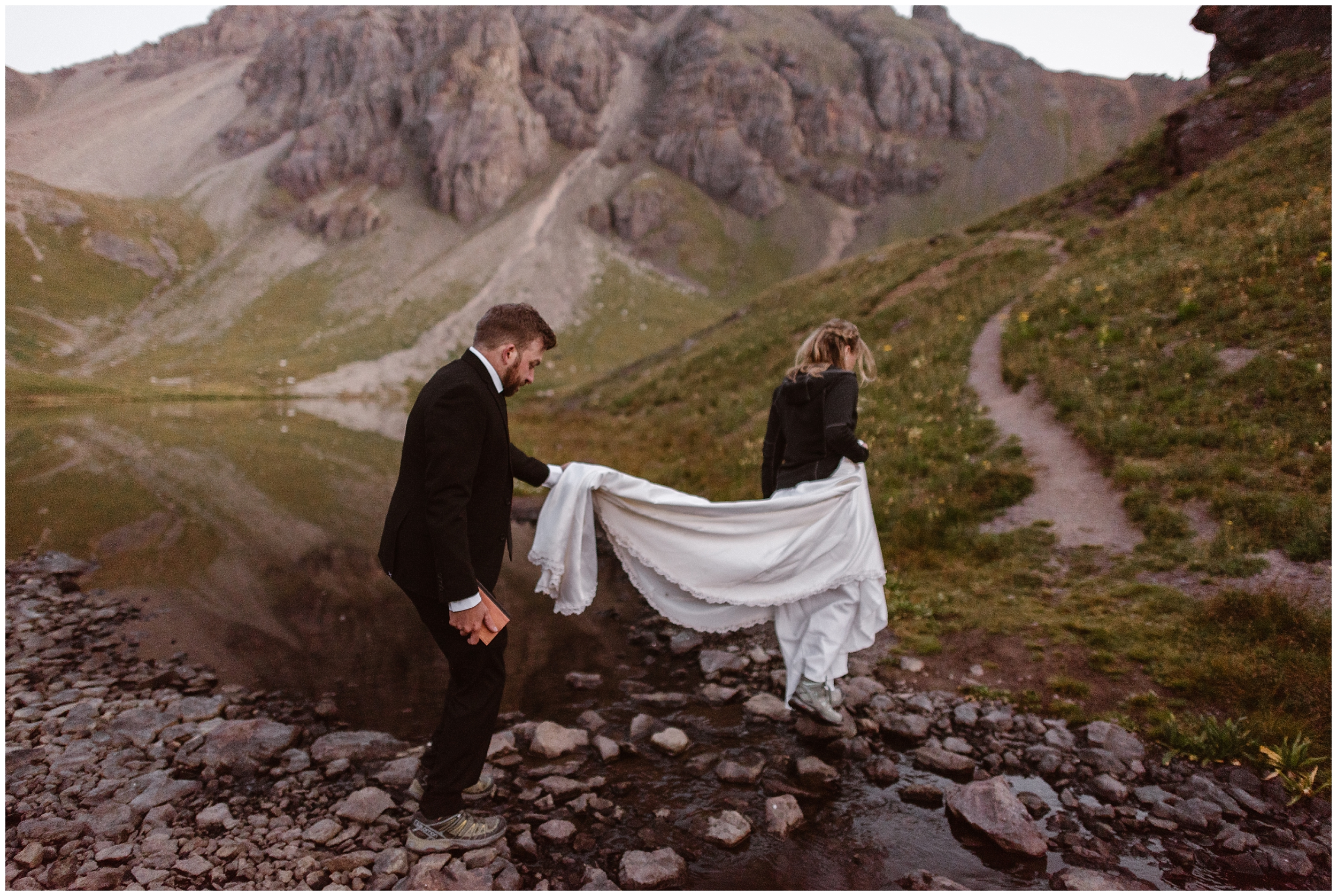 Nick holds back Brecka's wedding dress as they cross over a stream while hiking to the spot they chose for their elopement ceremony. This Colorado mountain wedding was the small simple wedding they both wanted.
