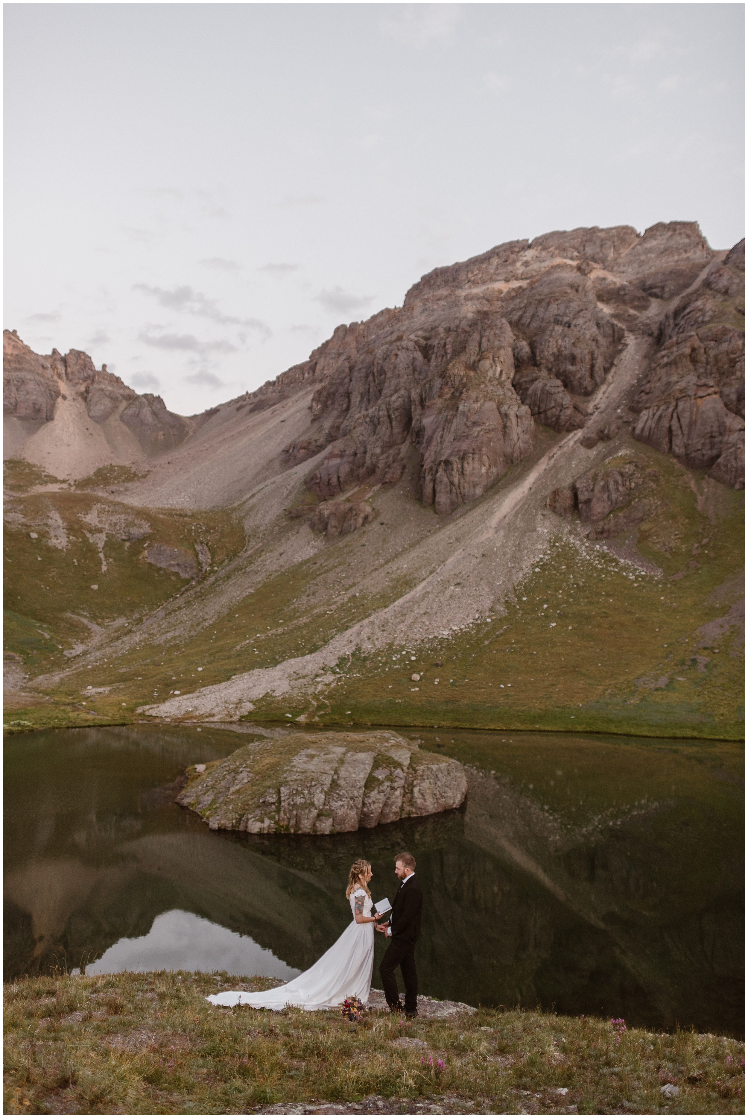 Brecka and Nick, the bride and groom, stand in front of an alpine lake as they read their vows to each other during their elopement ceremony. The two of them wanted an intimate adventure elopement in the Colorado mountains together. That's one of the benefits of eloping — you can have exactly the destinatino wedding you want!