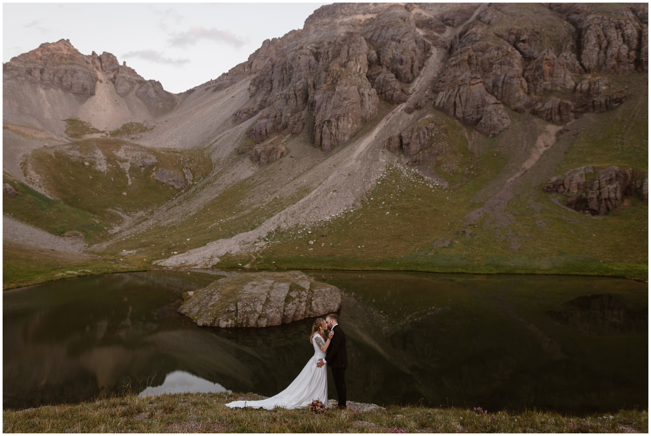 Standing in front of a deep blue alpine lake, Brecka and Nick, the bride and groom, embrace and share their first kiss as a couple. Hiking on your elopement day is one of hte best elopement ideas for adventurous couples who want a destination elopement.
