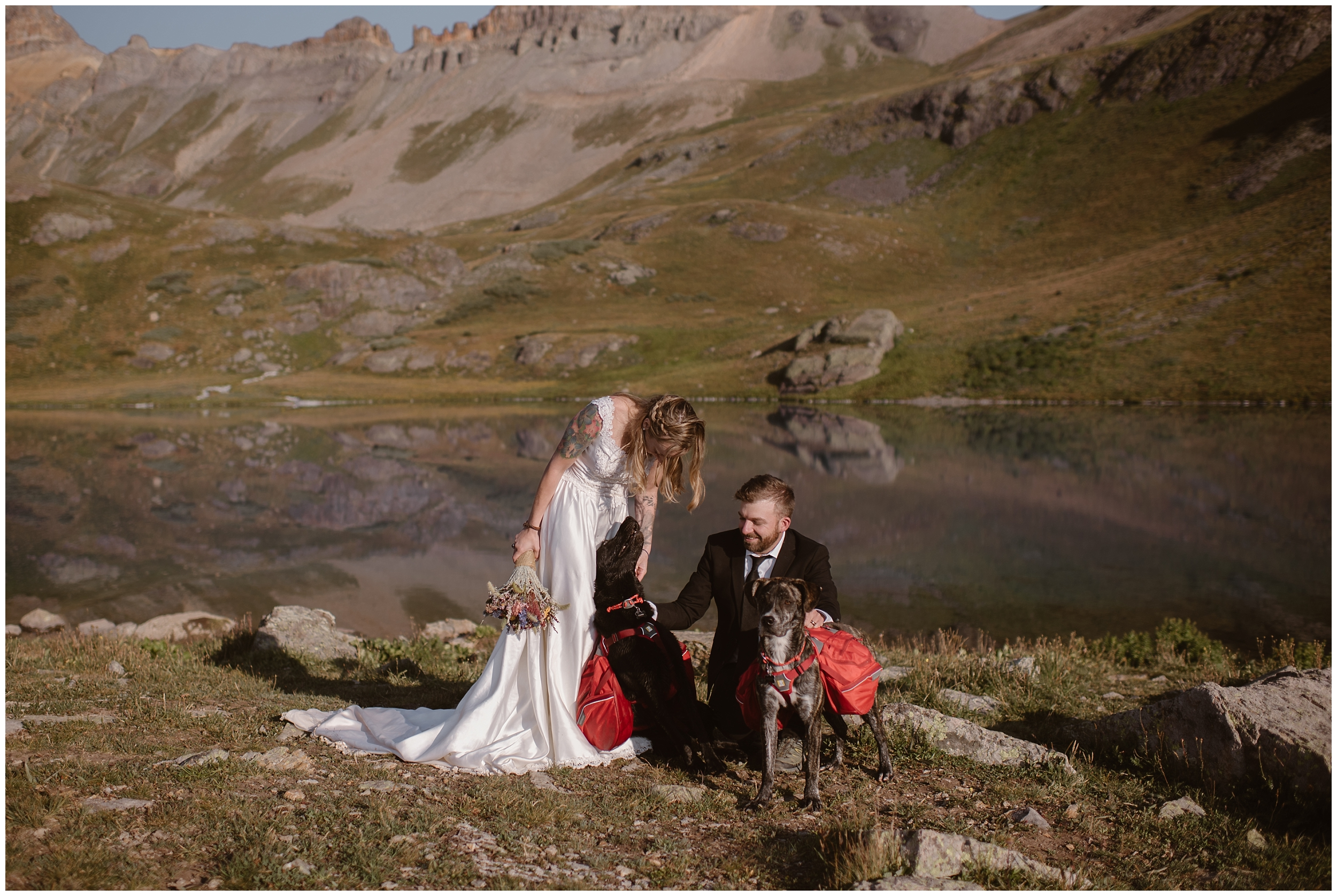 The bride and groom pose next to a beautiful alpine lake with their two pups, Cooper and Trek. Eloping with dogs is totally possible! If your pup is important to you, include them in your small simple wedding like Brecka and Nick did for their Colorado adventure elopement.
