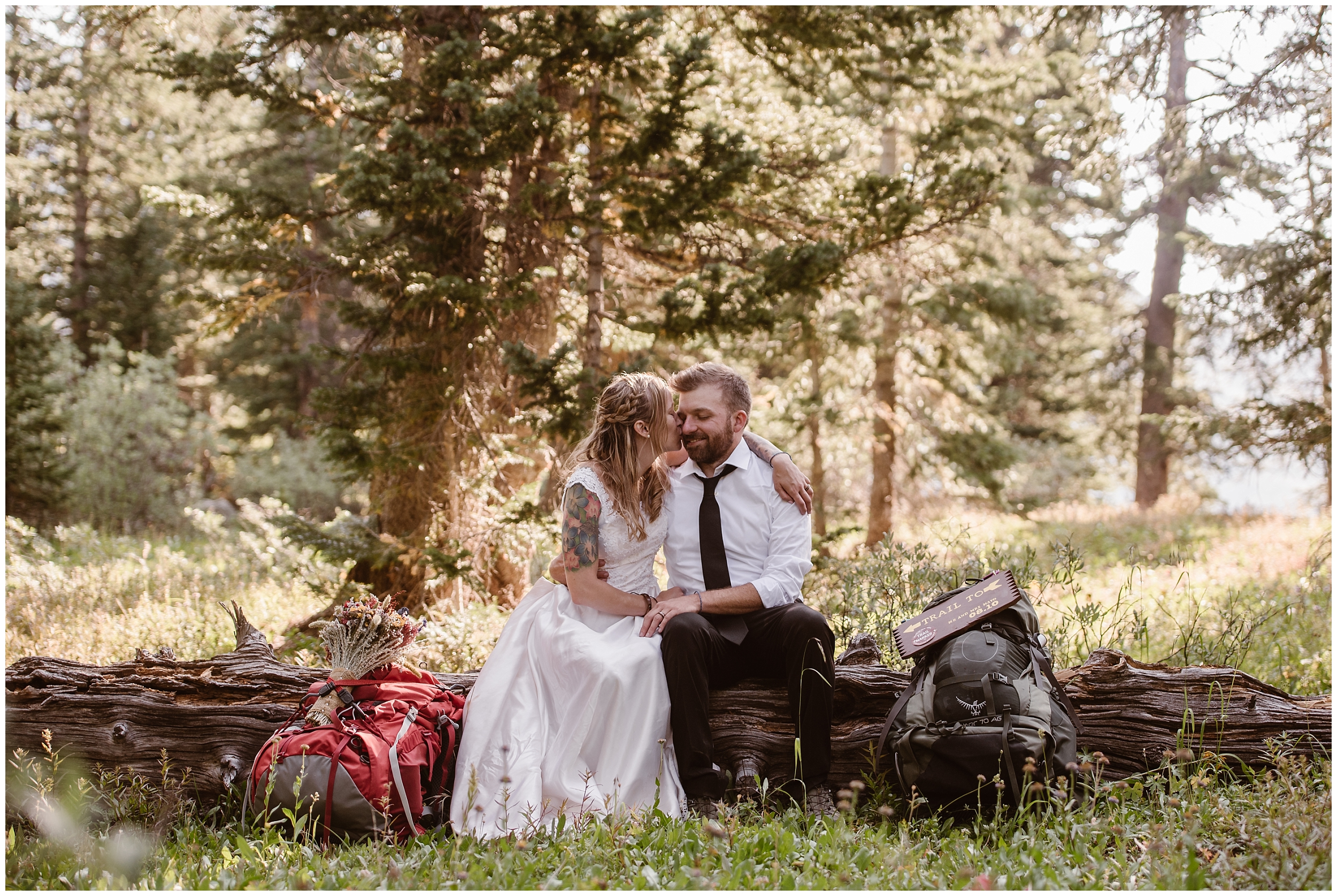 The newly married couple sits on a log in the Colorado forest, taking a break as they hike down for their elopement ceremony locaion spot. Surroudned by green forests, they embrace and kiss.