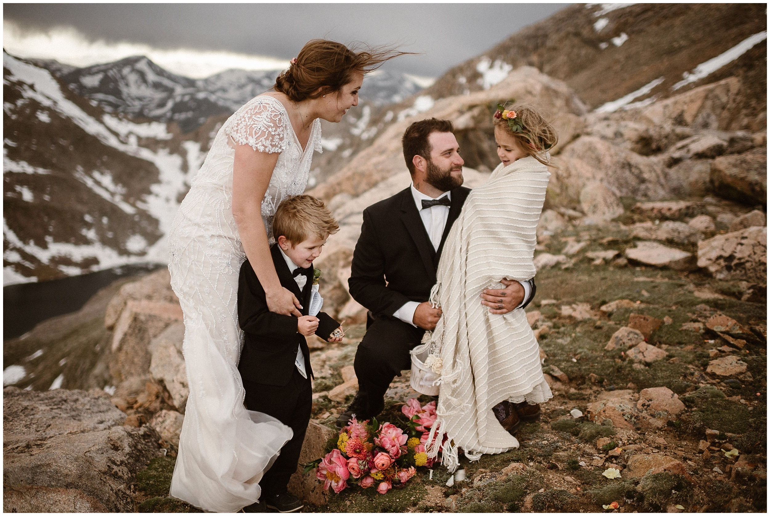 A bride, a groom, and their two children stand at the top of a mountain, huddled together in this elopement picture captured by elopement wedding photographer Adventure Instead. Behind them, mountain peaks covered in snow can be seen.
