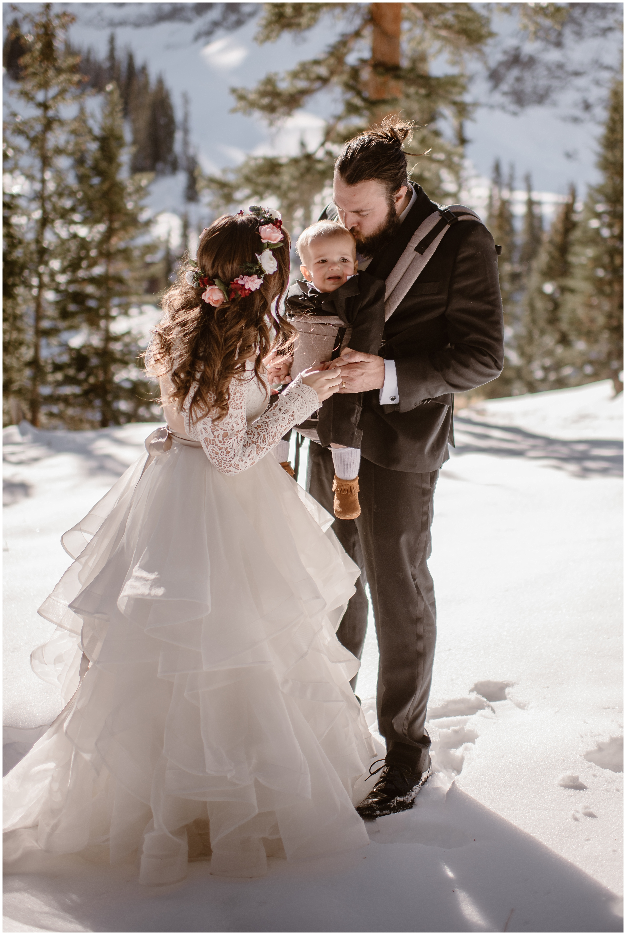 A bride leans in to kiss aher baby who is being held by her groom. The baby, strapped into a carrier on the groom's chest, looks around at the snowy ground and evergreen trees. Eloping with kids can be ias involved as you want!