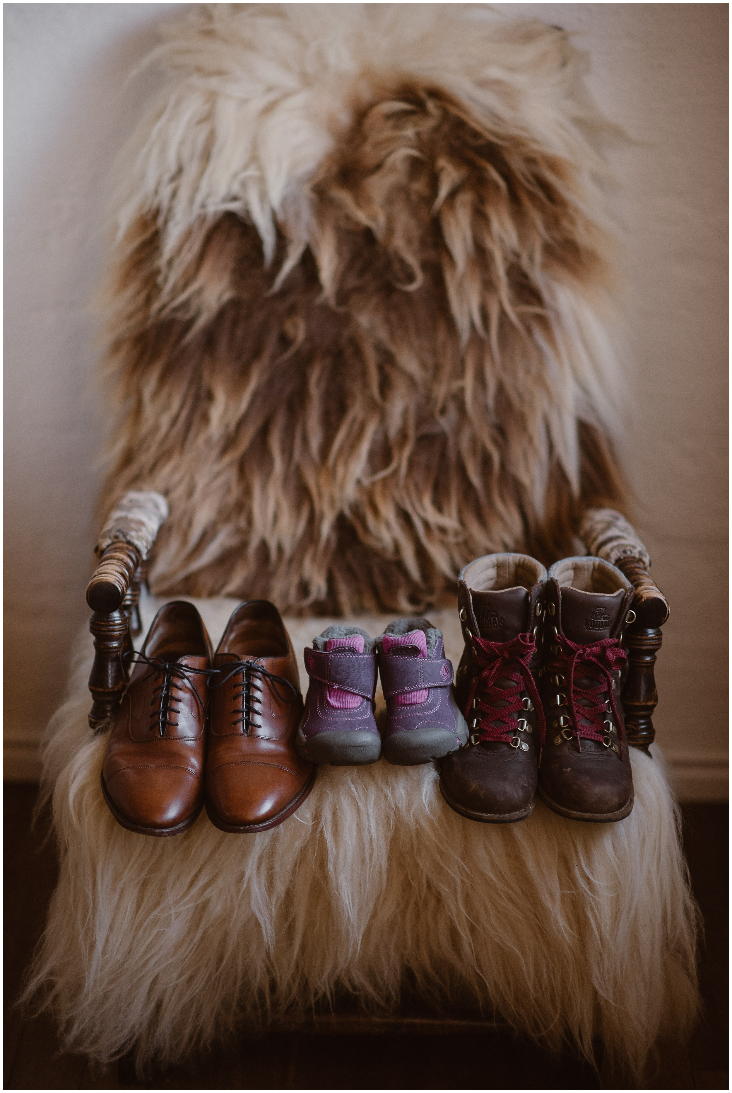 A furry, fuzzy chair is shown in this picture captured by elopement wedding photographer Adventure Instead. On the chair sit three pairs of shoes — men's dress shoes, hiking boot,s and a pair of tiny child's shoes. Including your child in your small simple wedding can mean incorporate your own unique eloping ideas.