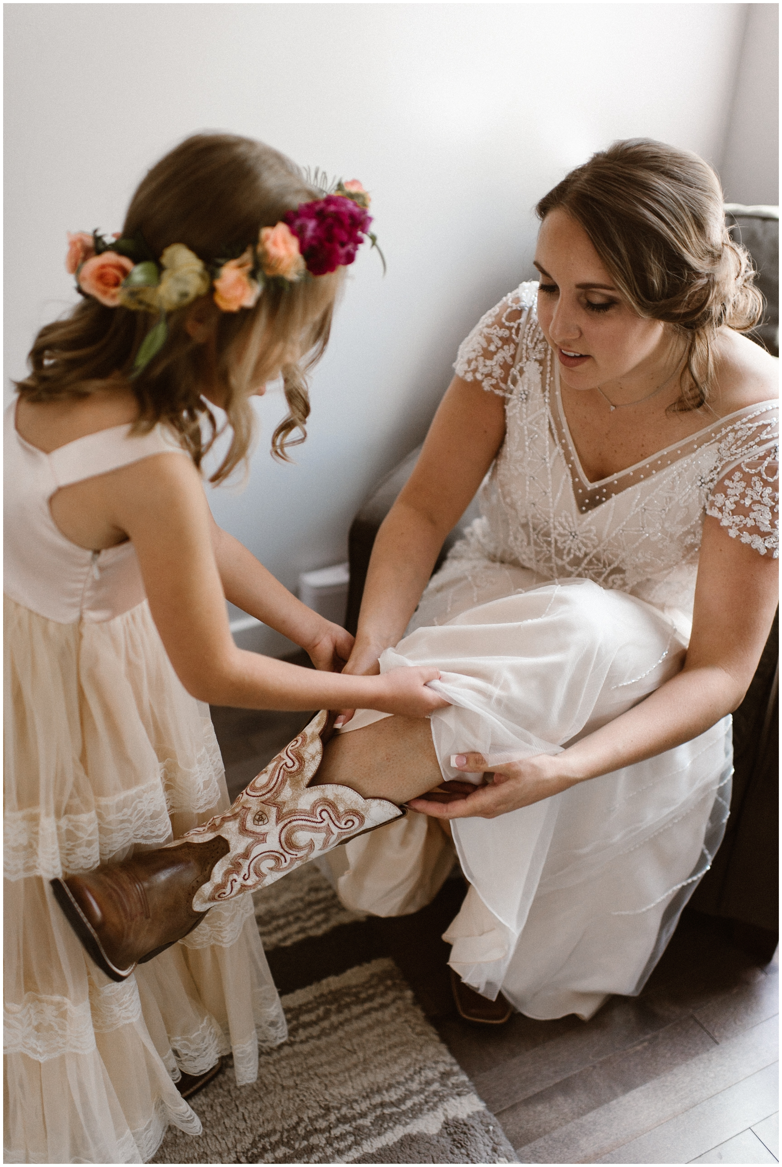 A yound child helps her mother get ready as she puts on her cowboy boots. Including your child in your elopement ceremony can happen anyway you want, even if it means just helping you get dressed up for your big day!