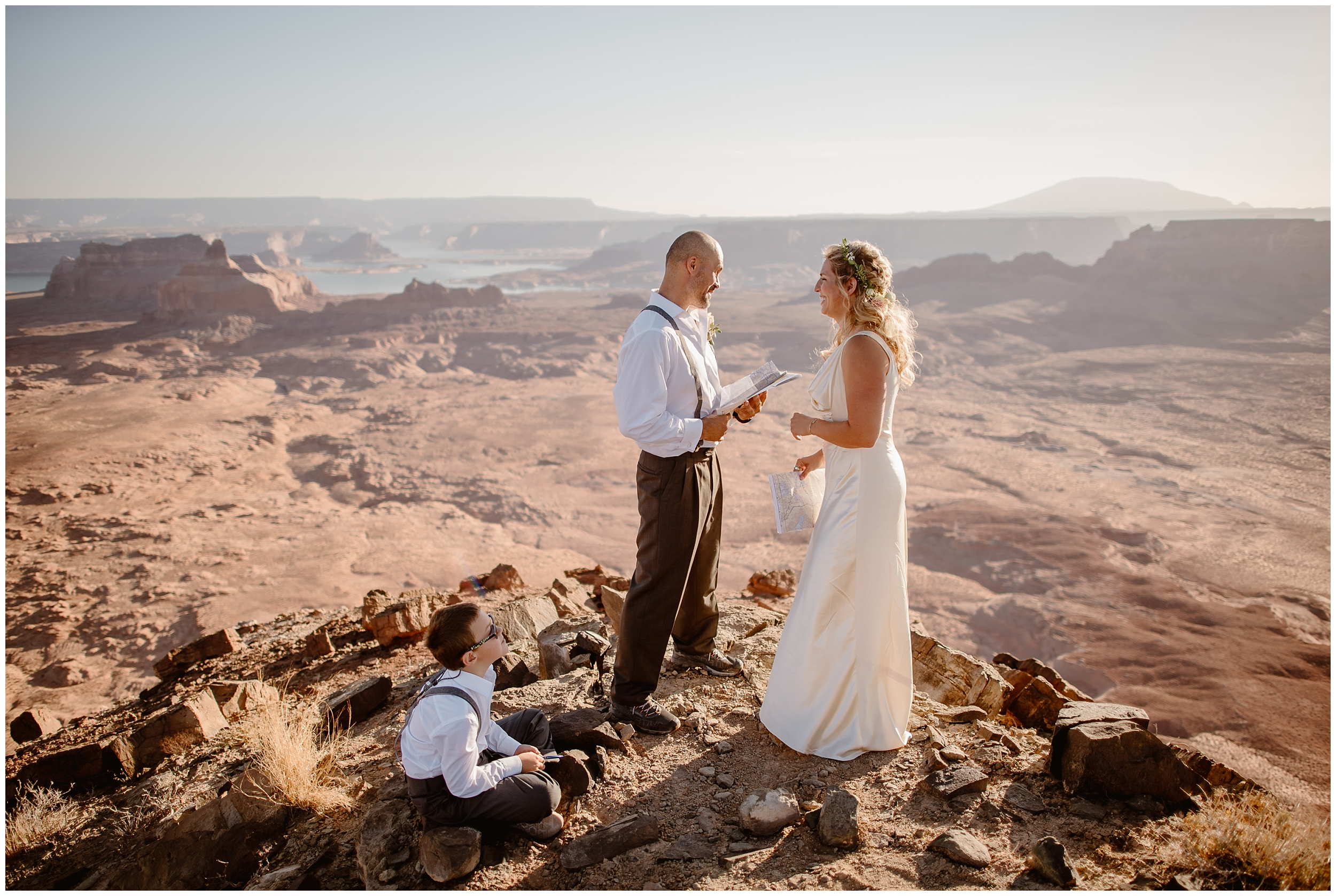 A young boy sits at his parents' feet at the top of a canyon in the Southwest as they read their vows during their elopement ceremony. These adventure elopement pictures were captured by elopement wedding photographer Adventure Instead.