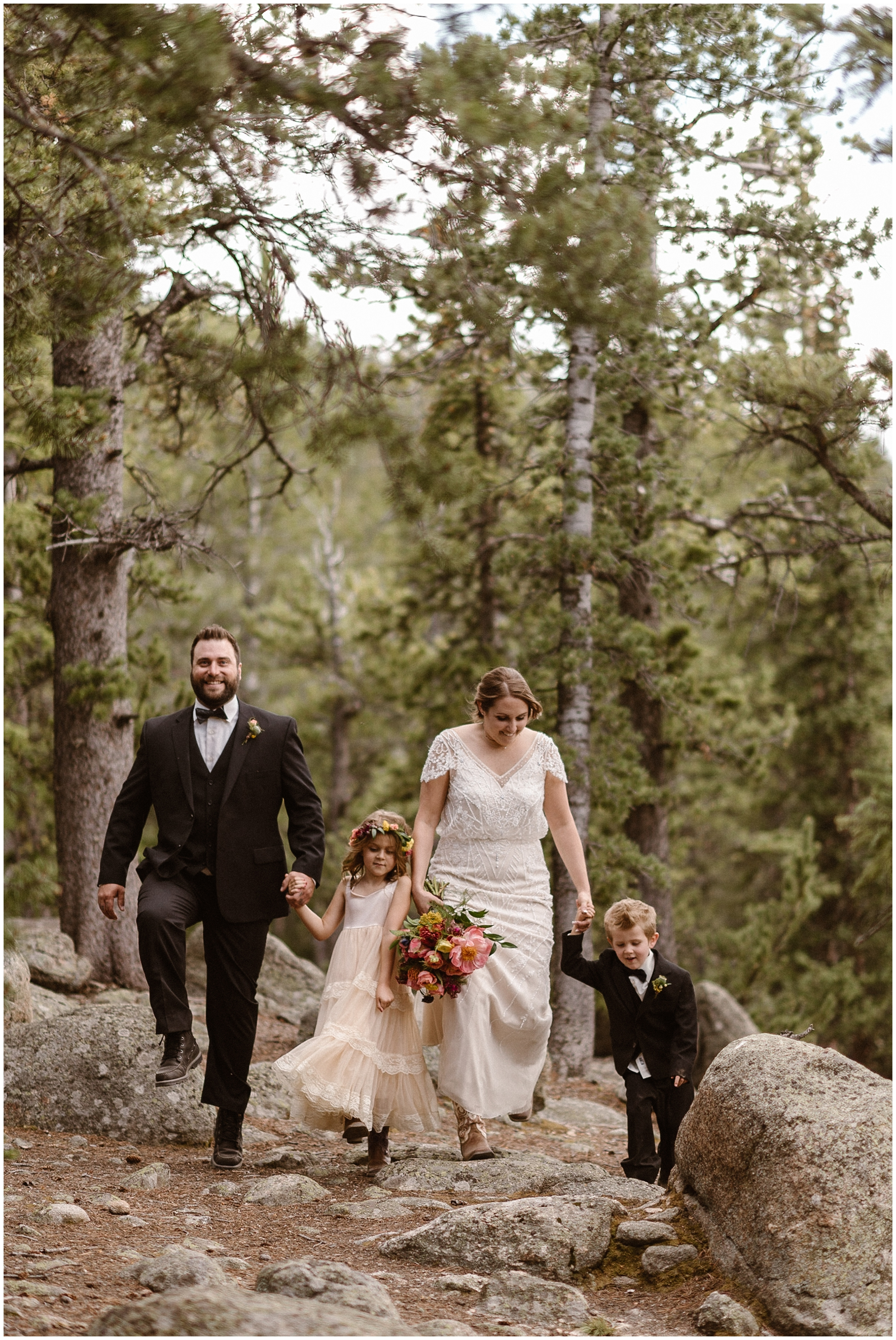 A bride, a groom, and their two children hike down a trail together in their wedding attire! When you choose to elope with kids, you can make your day as adventurou as mild as you want — just be sure to have the elopement day you want!