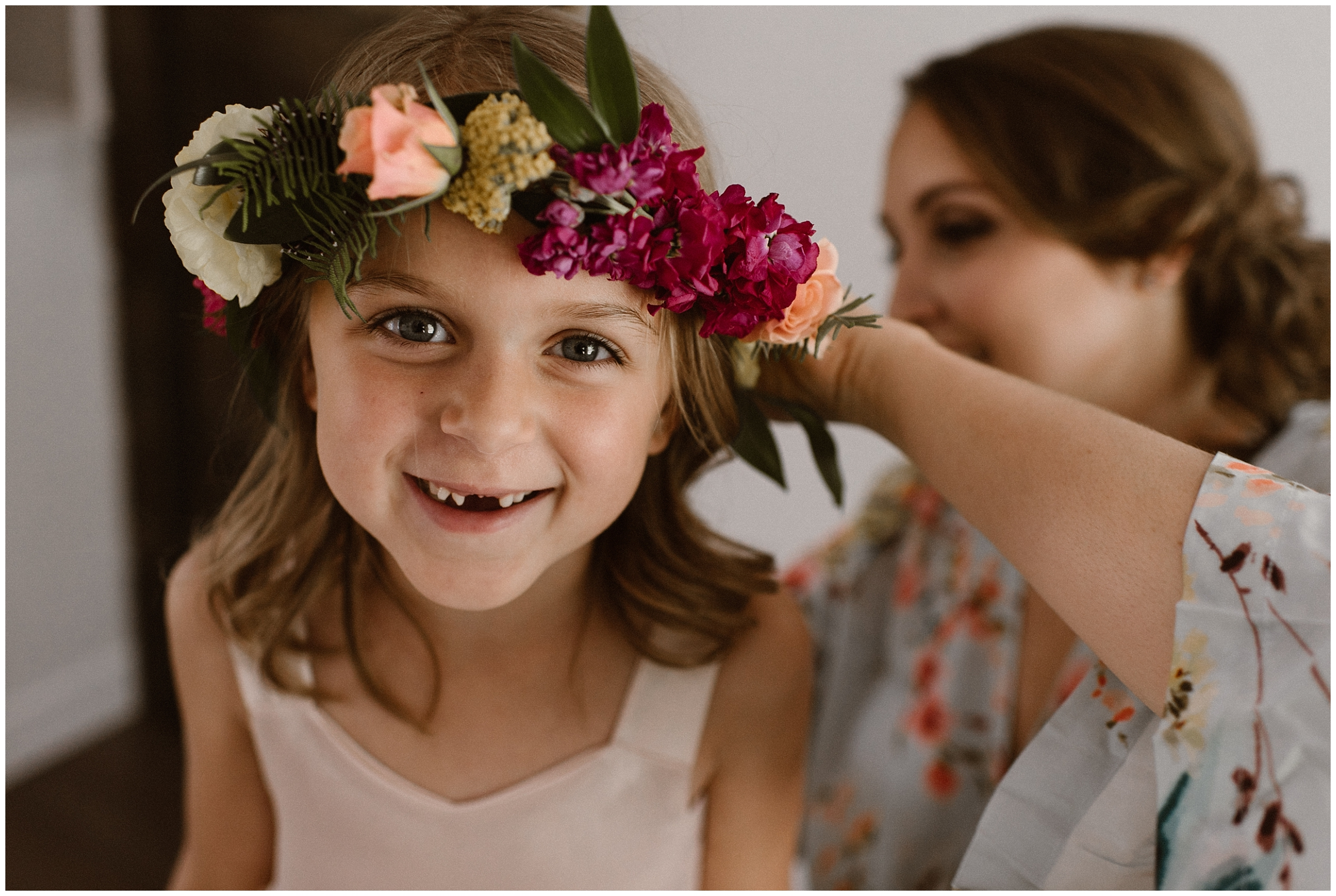 A mother (the bride) helps her daughter adjust her flower crown. The little girl, sporting a toothless grin, looks up at the camera in these elopement photos captured by Adventure Instead, an elopement wedding photographer.
