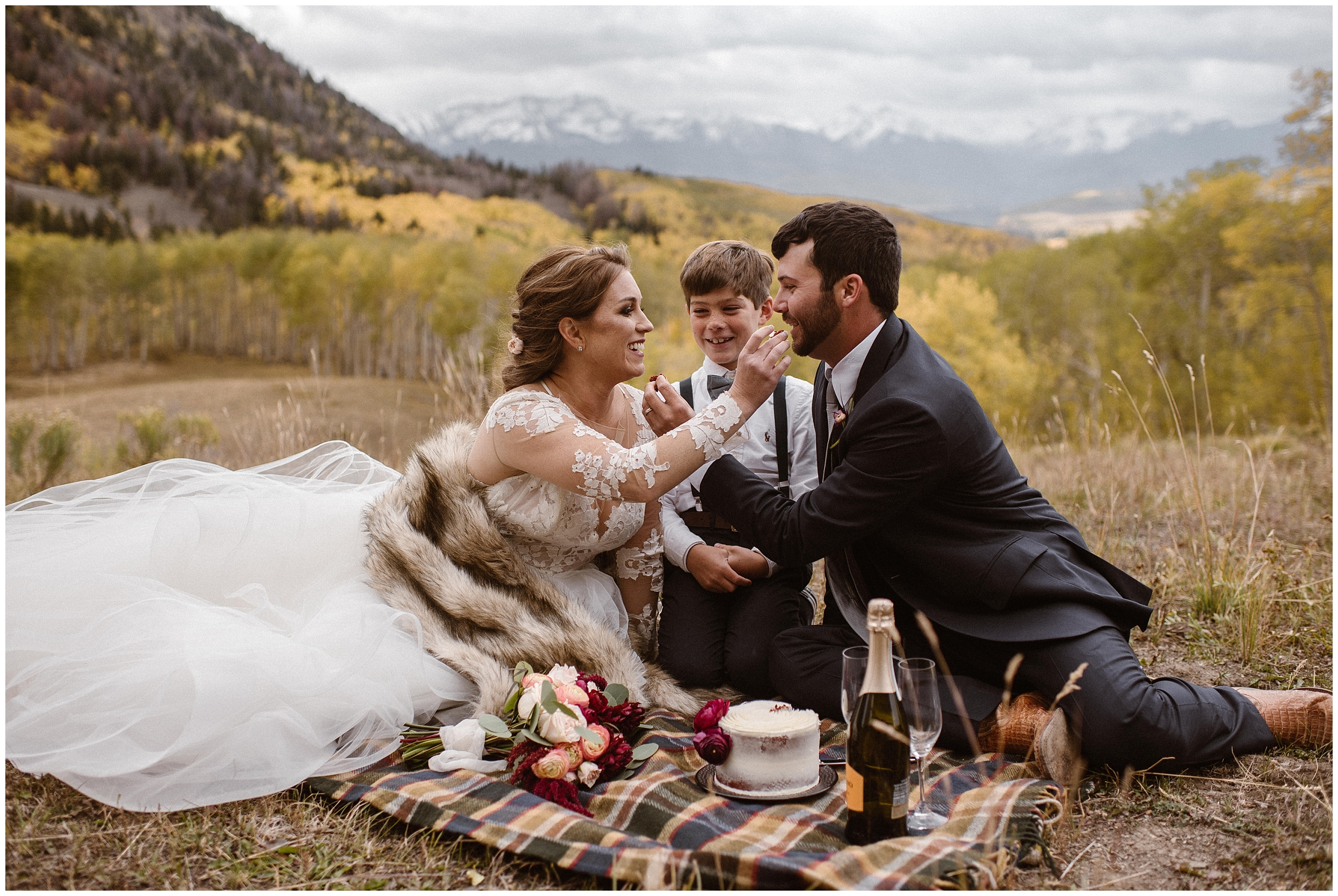 A young boy sits in the middle of a bride and groom on acheckered blanket during the reception after eloping. The bride and groom are feeding each other snacks while the boy looks on, laughing.