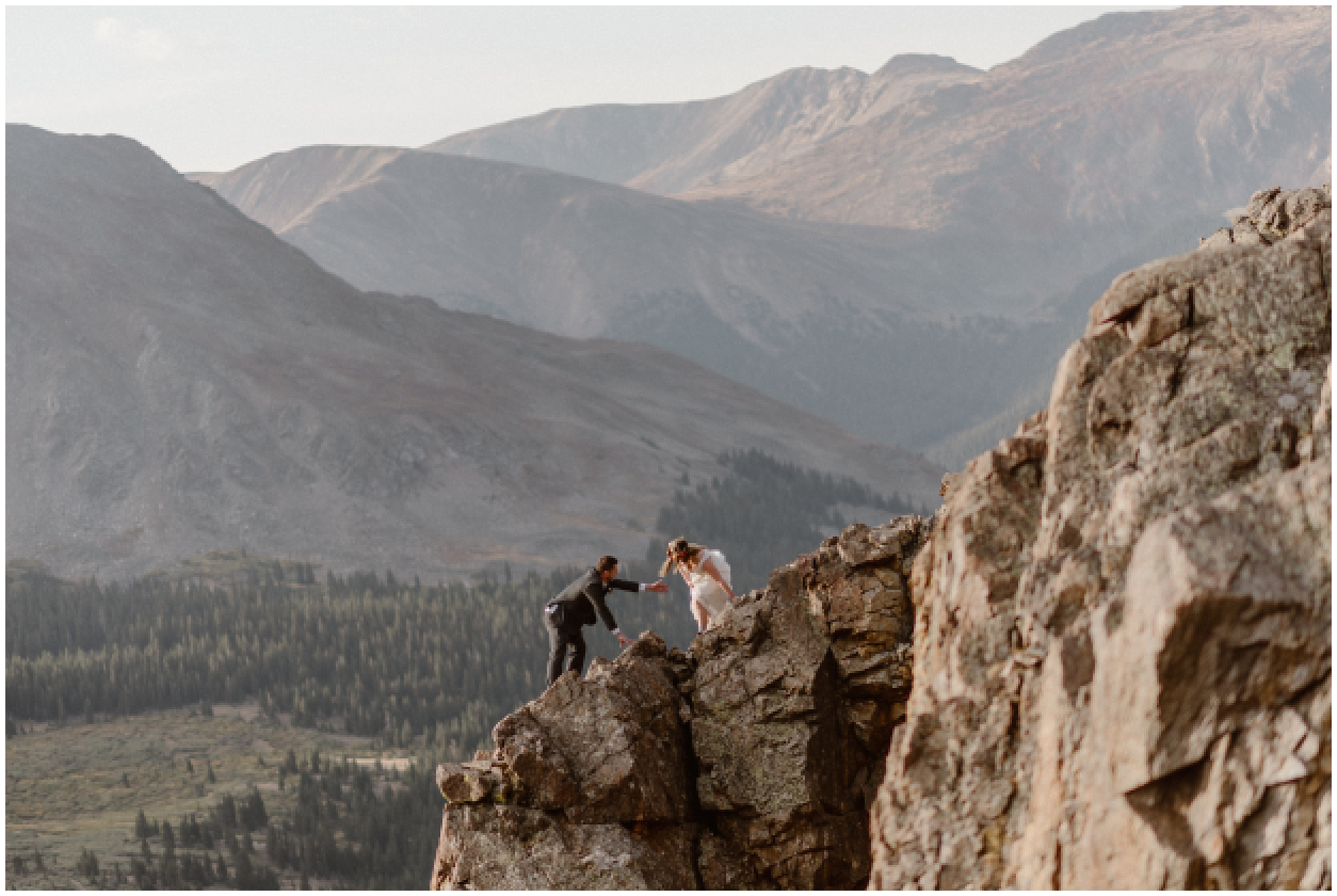 A bride and ag room take hands as they scramble up the side of a mountain together in their wedding day attire. Behind them, giant mountain ranges and Colorado forests can be seen. This destination wedding was the elopement location of this couple's dreams and was the perfect place to have their Colorado mountain wedding.