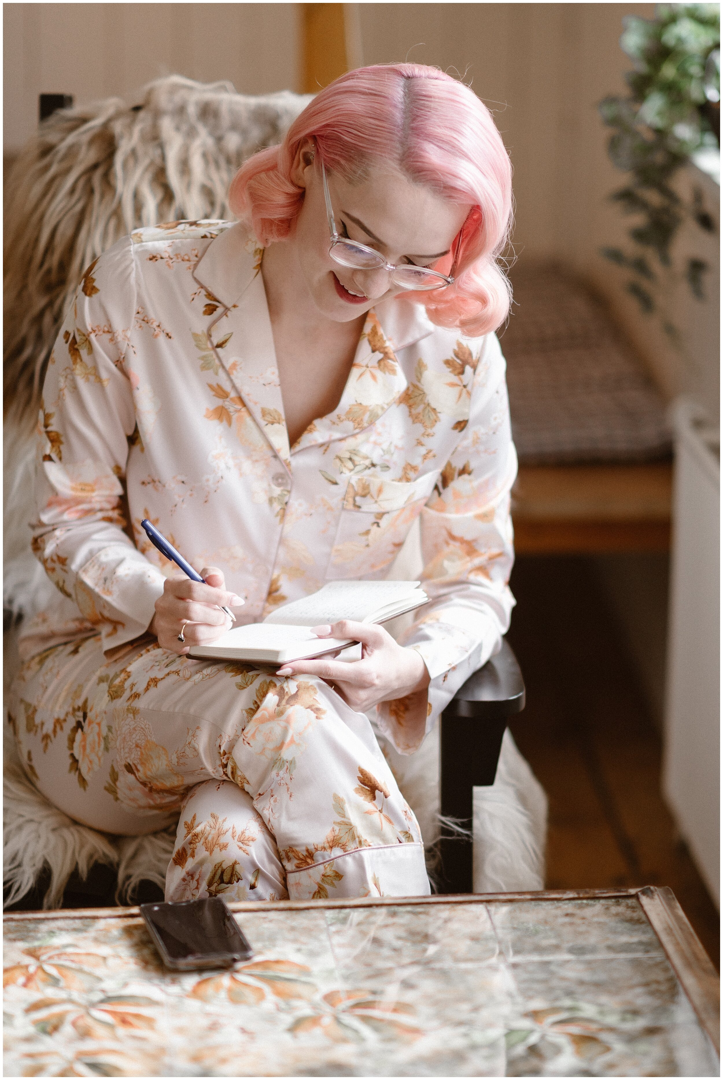 The bride, Elaura, writes in her handmade vow book as she reflects on what she'd like to say to her almost-husband, Daryn, during their elopement ceremony. Elaura and Daryn's destination elopement in the Faroe Islands was all about their own vintage vibe, equipped with glass coke bottles, pastel pink hair, and handmade bows for Daryn's tux.