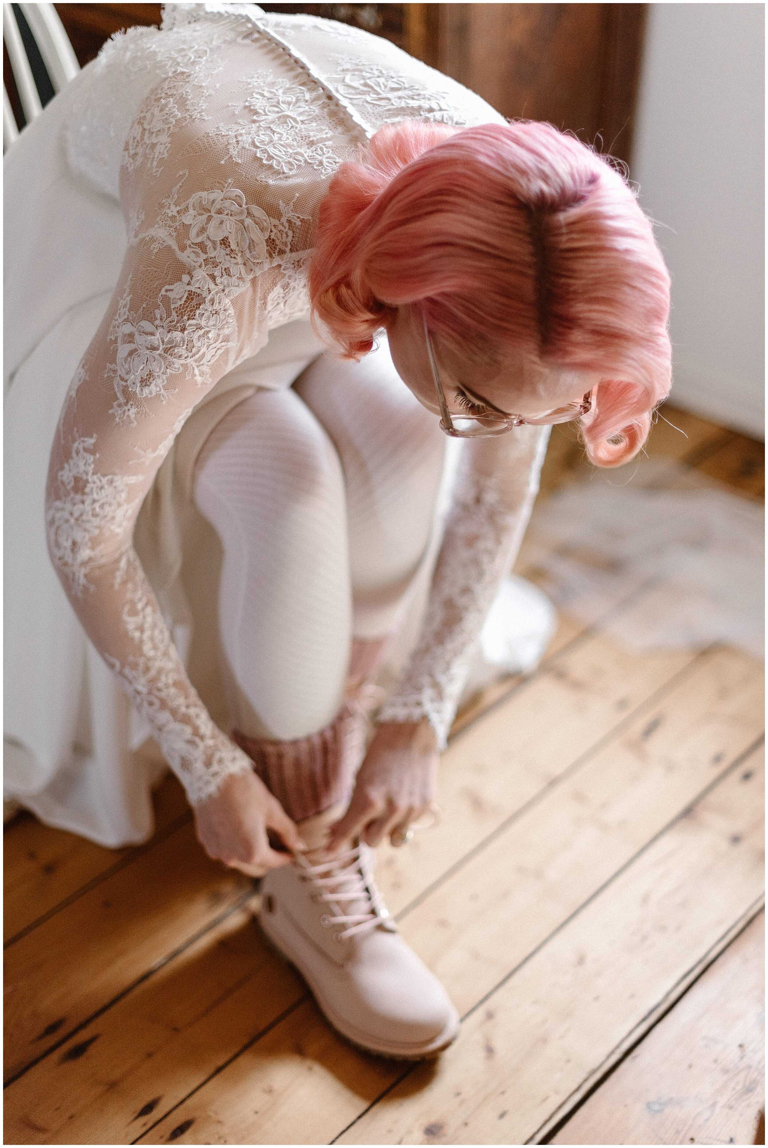 The bride, Elaura, leans down to tie up her pastel pink Justin boots as she finishes getting her vintage wedding look ready for her adventure elopement in the Faroe Islands. Elaura and Daryn's destination wedding in the Faroe Islands was exactly the mood the two Australians were going for — foggy, dramatic, and epic.