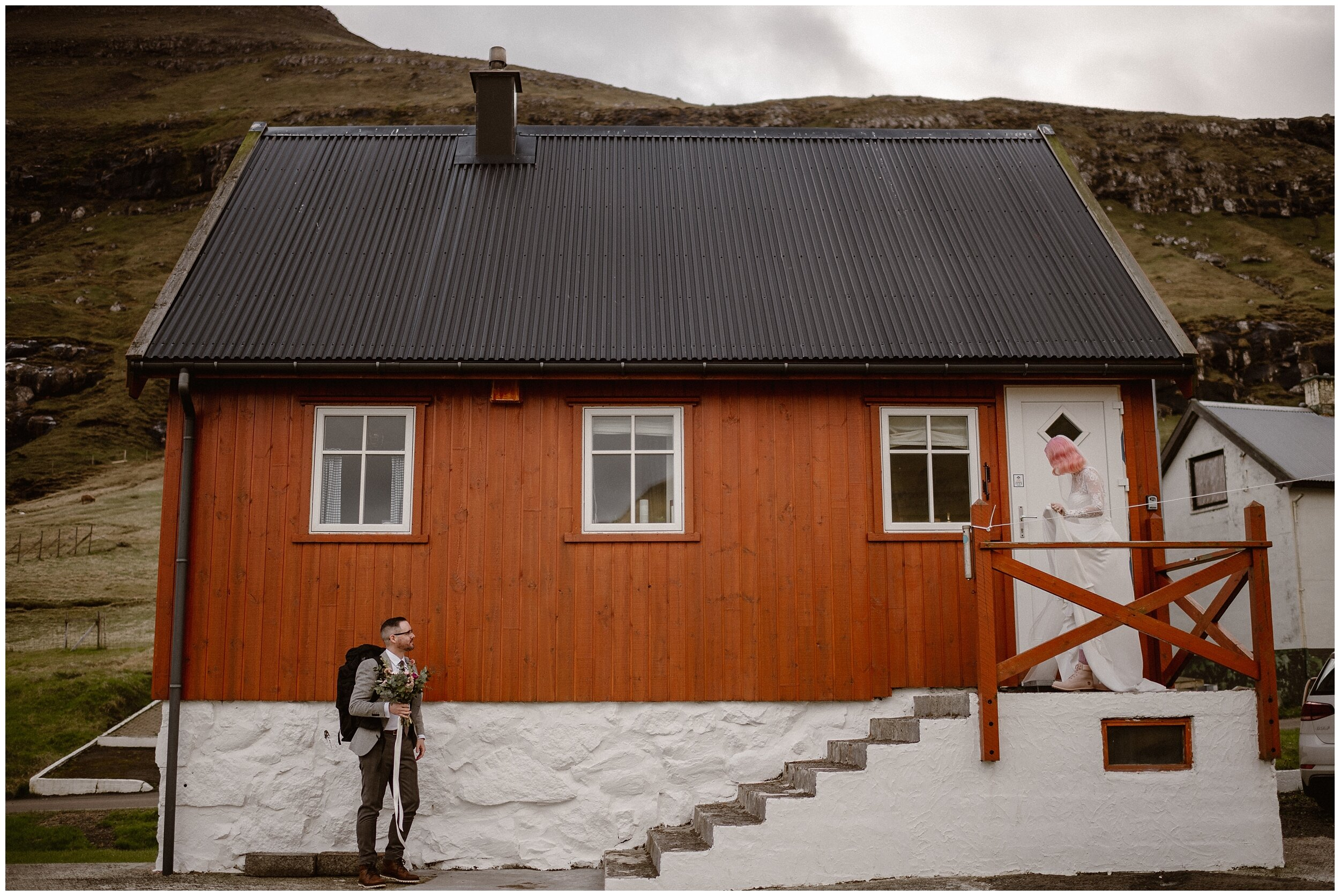 Elaura walks out of the Faroe Island Airbnb down the steps toward Daryn, who's holding her bouquet of flowers. These adventure elopement photos in the Faroe Islands were captured by Adventure Intead, a destiantion elopement wedding photographer.