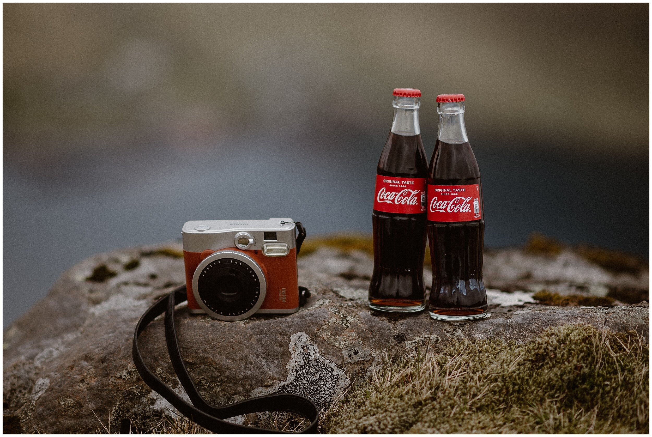 On a mossy rock sit two vintage coke bottles and a vintage polaroid camera, two very specific details of Elaura and Daryn's destination elopement in the Faroe Islands. These adventure elopement photos were captured by Adventure Instead, an elopement wedding photographer.