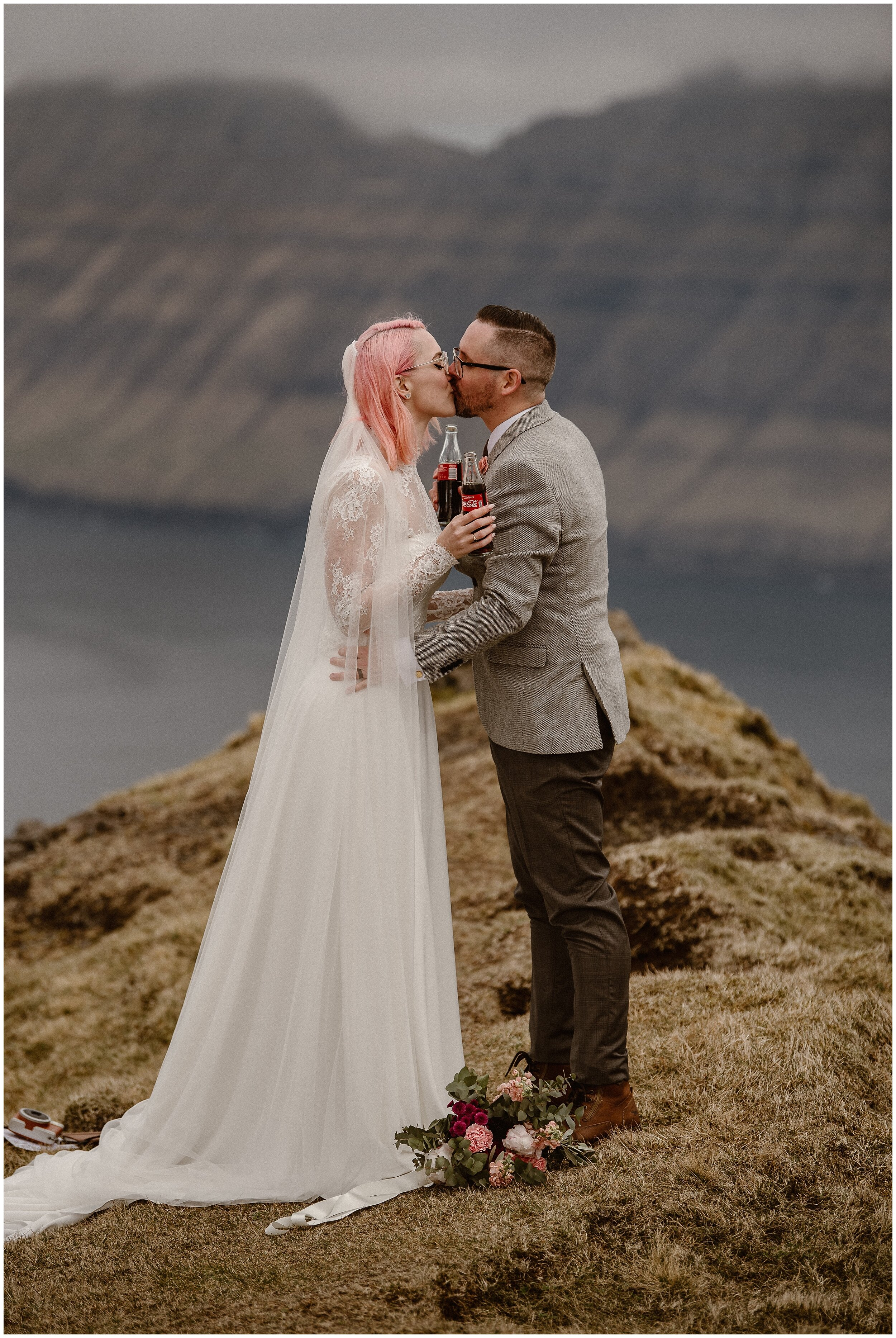 Bride and groom, Elaura and Daryn, hold each other close and kiss as they hold their vintage, glass Coke bottles in hand. Behind them, the epic, foggy, and gorgeous Faroe Island fjords can be seen amongst a misty water setting. These adventure elopement photos were captured by elopement wedding photographer Adventure Instead.