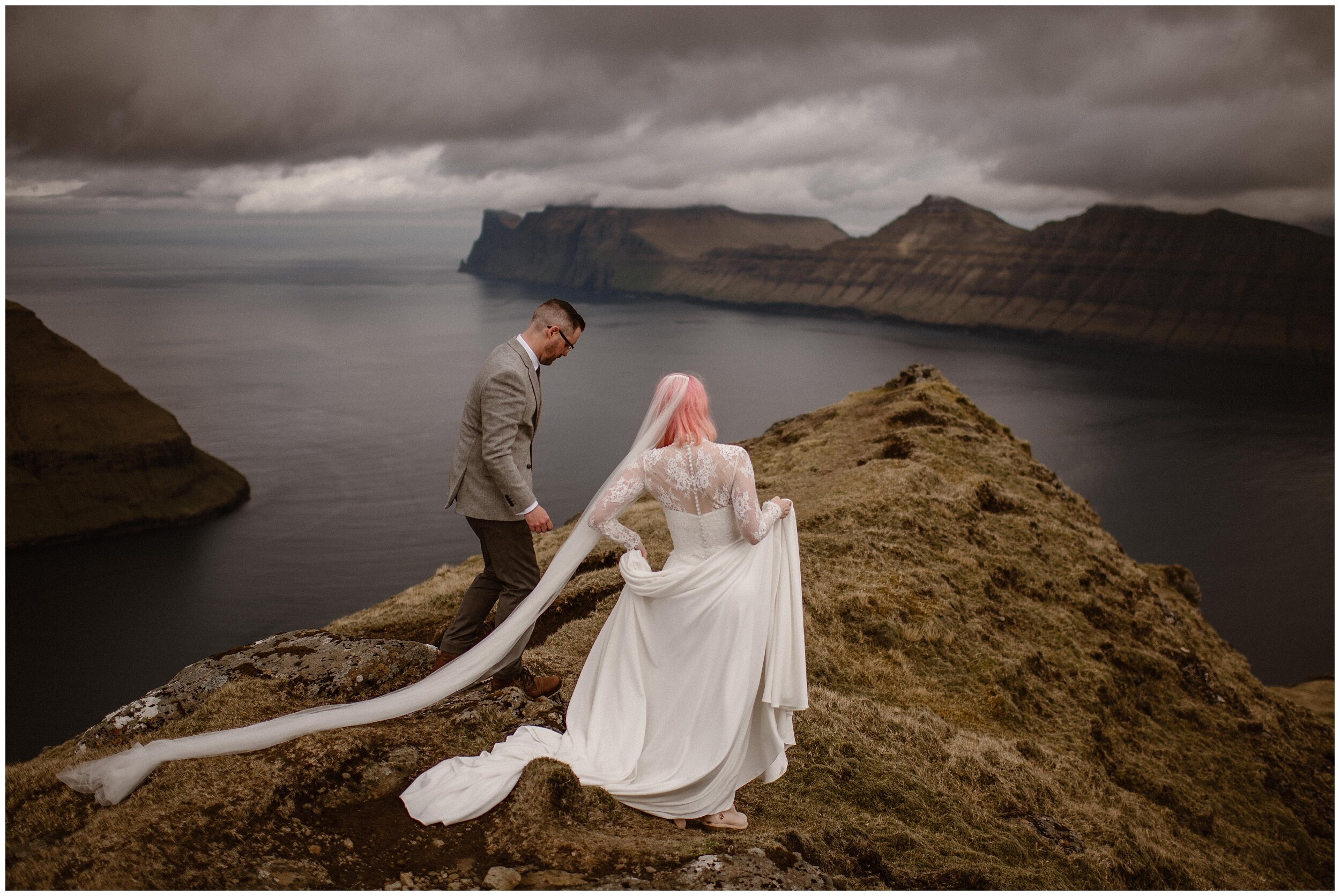 The bride and groom carefuly step out on the path toward the edge of a cliff overlooking a gorgeous Faroe Island fjord and waterscape. Elaura, the bride, lifts her custom-made wedding dress to reveal her pastel pink hiking boots. These adventure elopement photos were captured by Adventure Instead, an elopement wedding photographer.